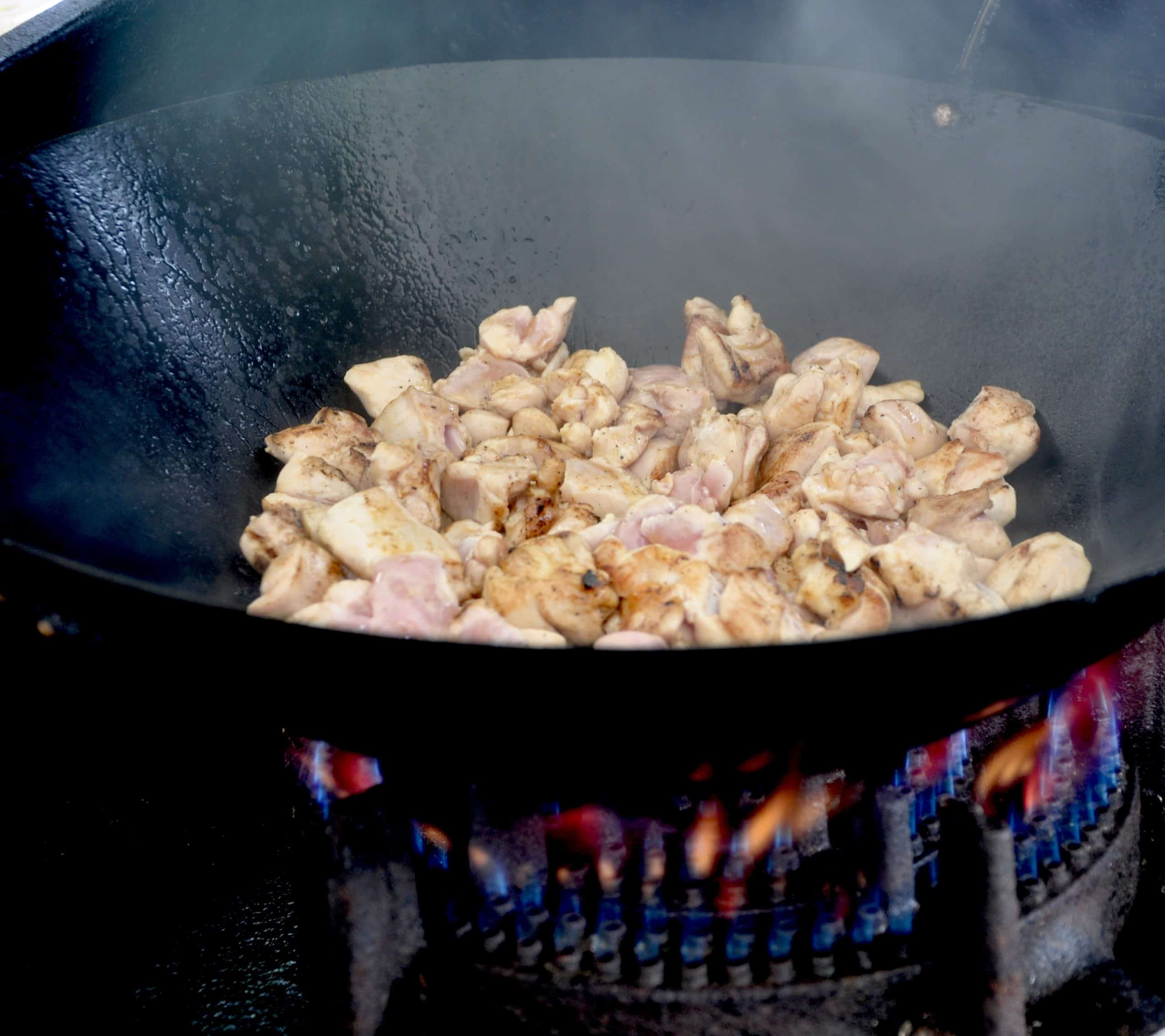 Chicken in wok over gas flame