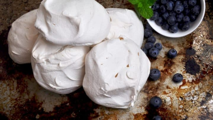 Meringue nest on metal tray with blue berries
