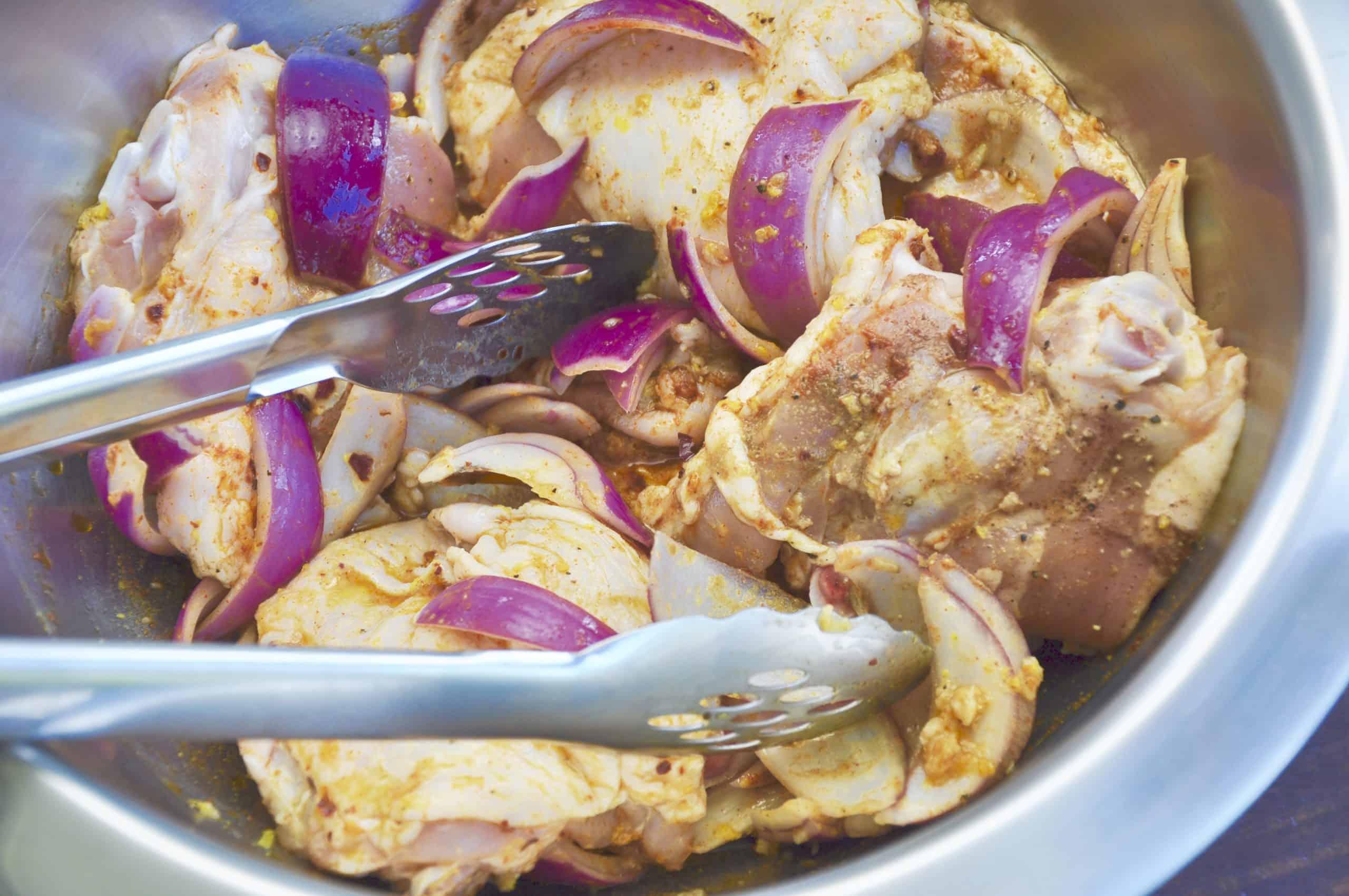 chicken shawarma marinade ingredients in a bowl with fresh chicken being added