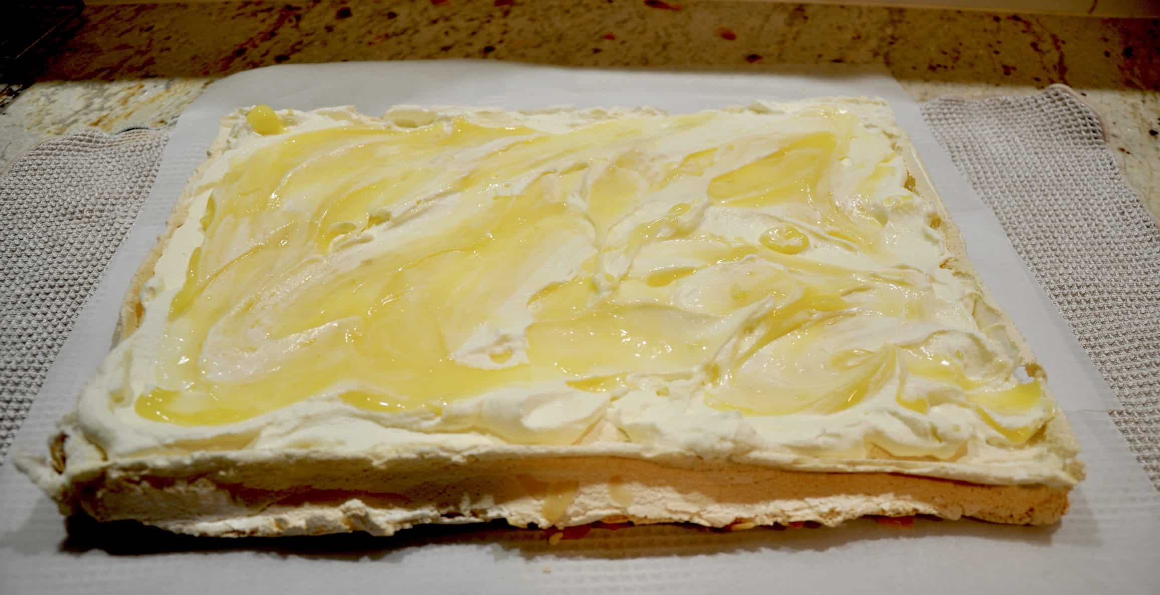 lemon curd and almond rolled pavlova spread with cream and lemon curd ready to roll