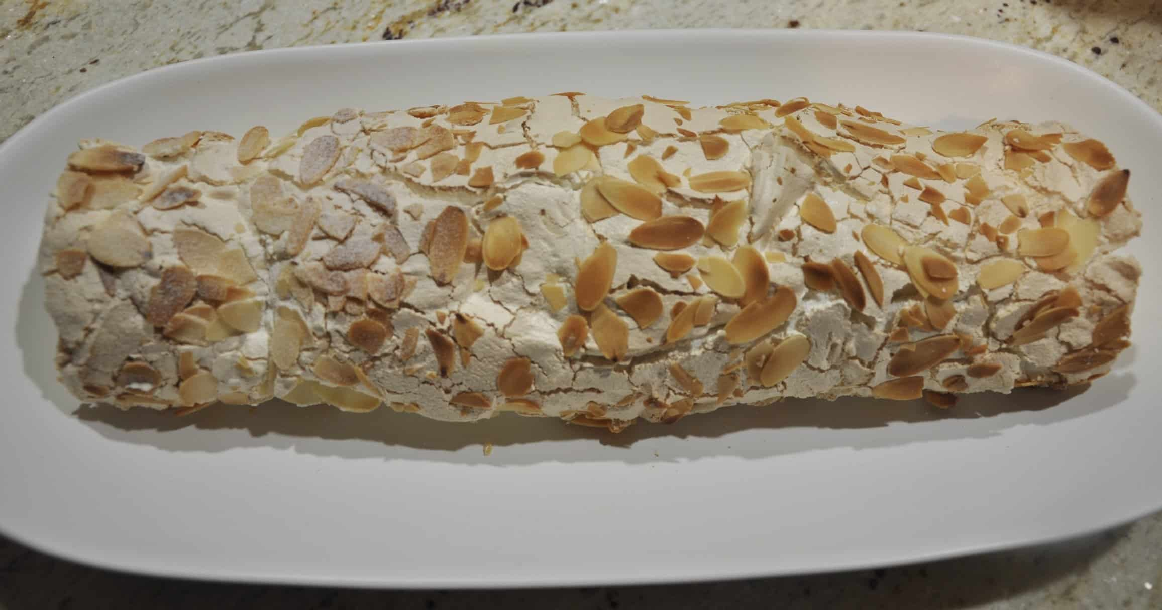 emon curd and almond rolled pavlova finished rolling on a white platter