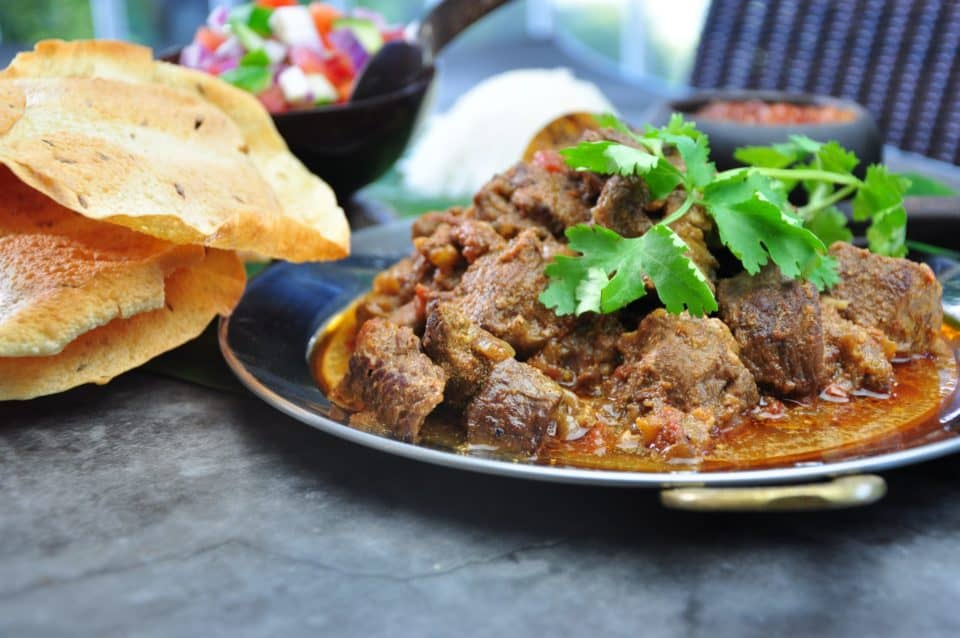 indian madras beef curry served on a plate with pappadam and rice and tomato salad in the background garnished with coriander