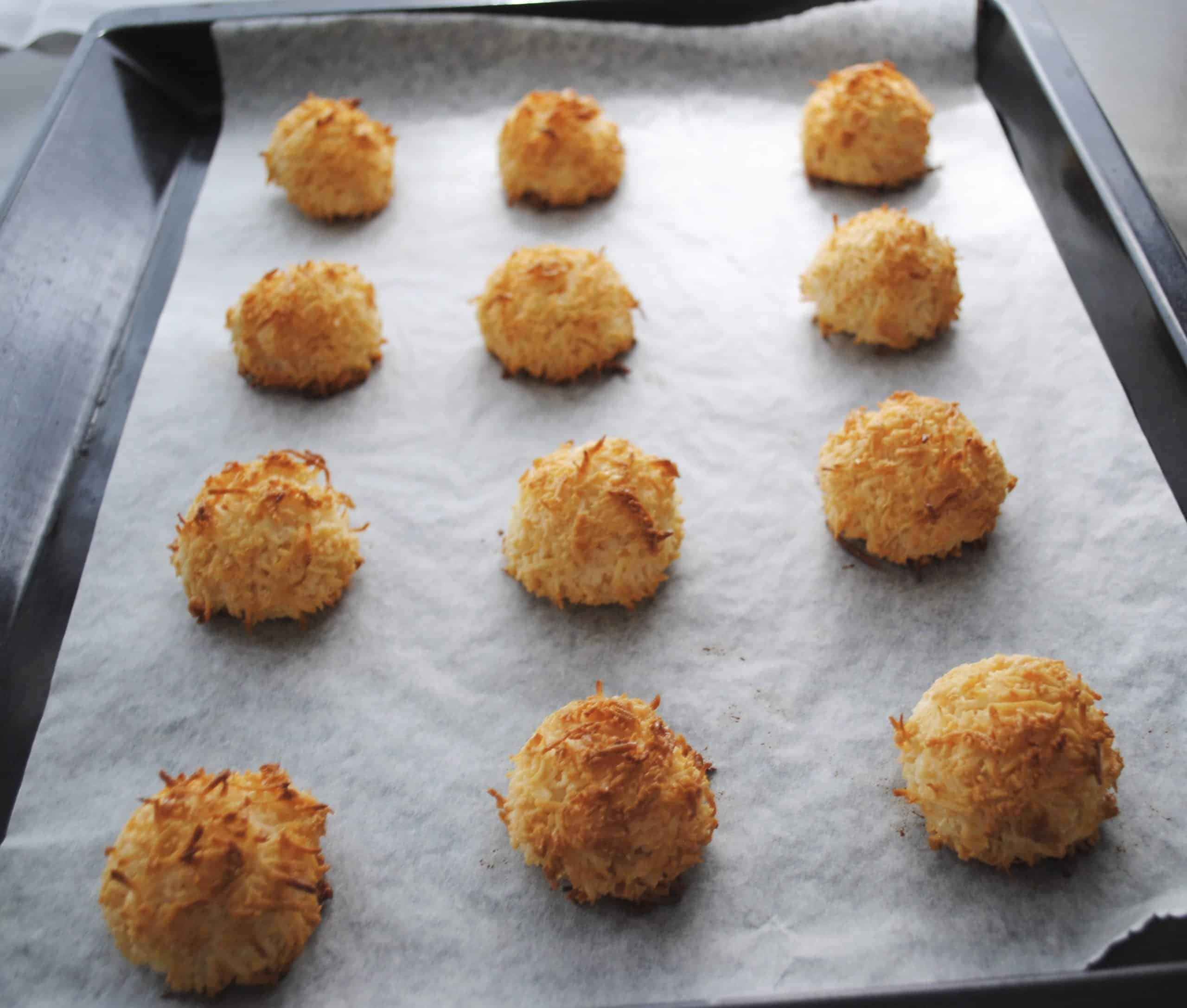 chocolate dipped coconut macaroons on black baking tray freshly baked and golden