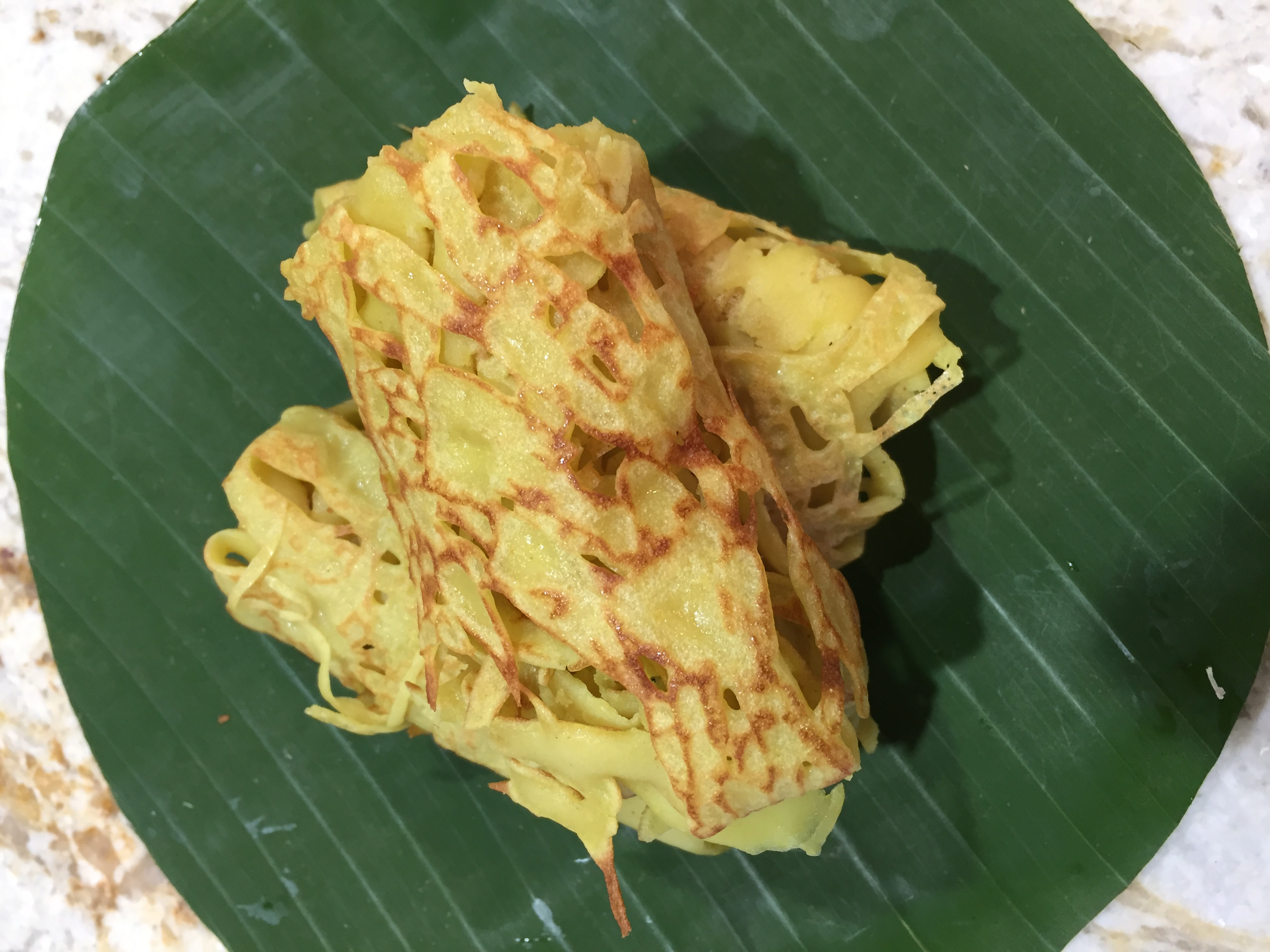 roti jala malaysian net pancake cooked and served on a banana leaf