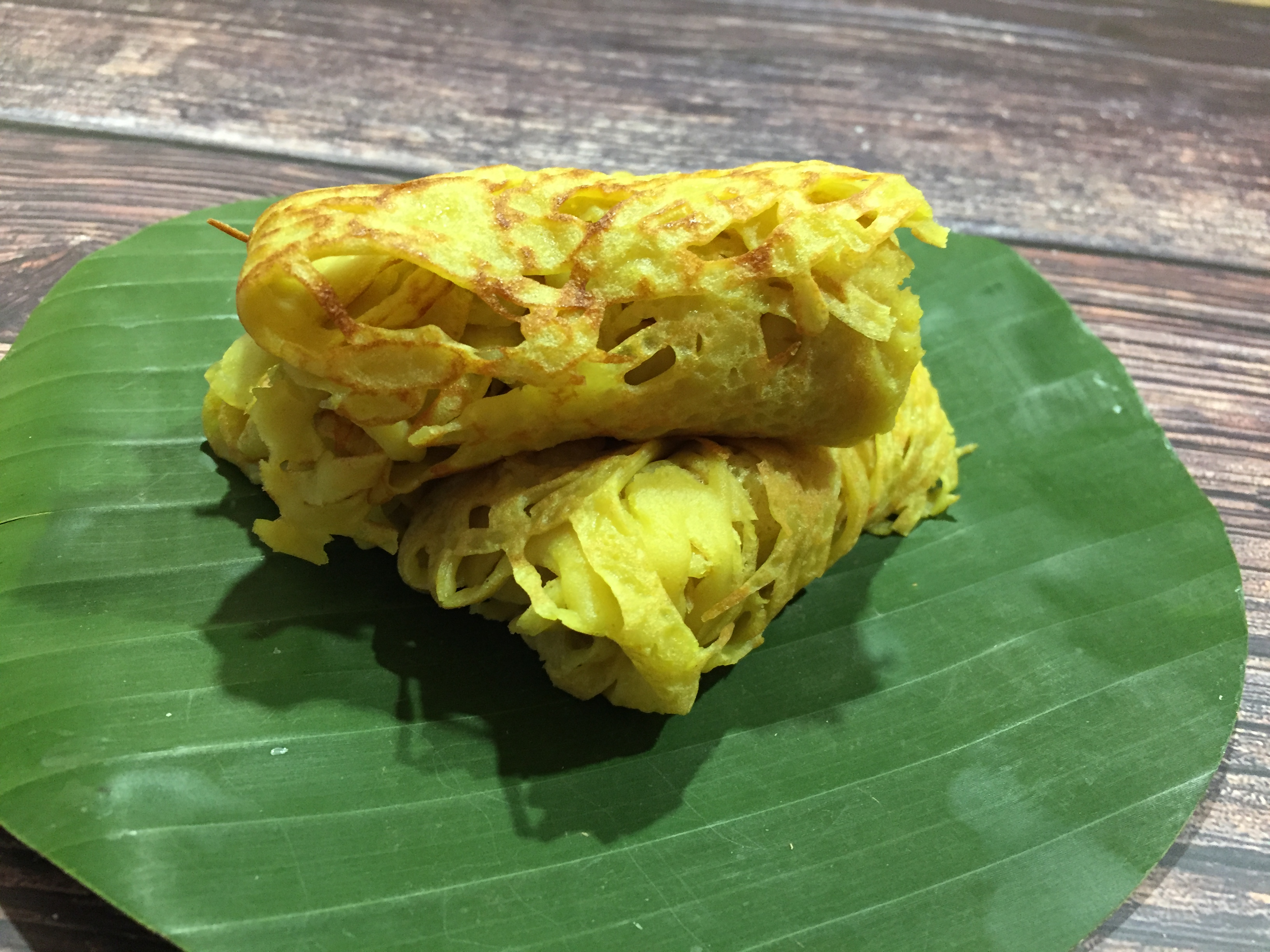 roti jala - malaysian net pancakes cooked and rolled served on a banana leaf