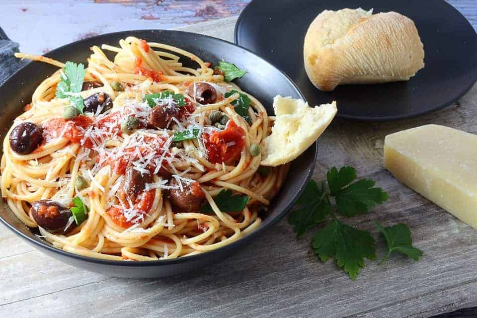 plate of puttanesca pasta on a timber board with crusty bread on the side