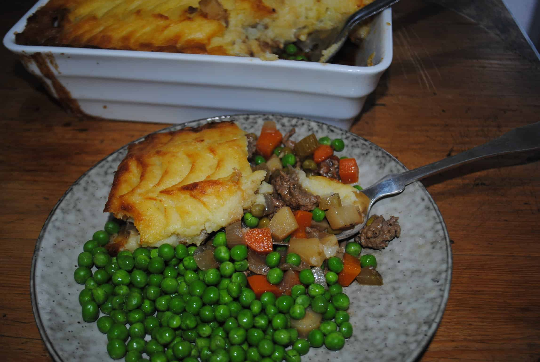 shepherds pie - in background with a serve on a plate with peas in the foreground