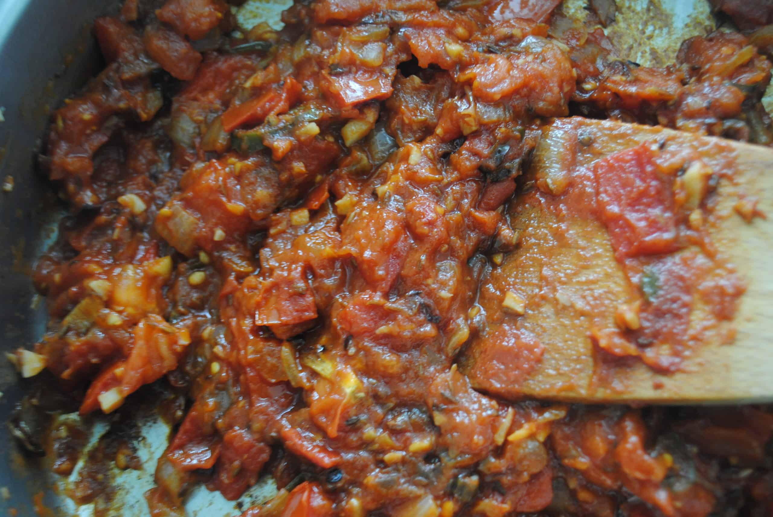 indian vegetable curry adding tomato paste to cooked ingredients in wok