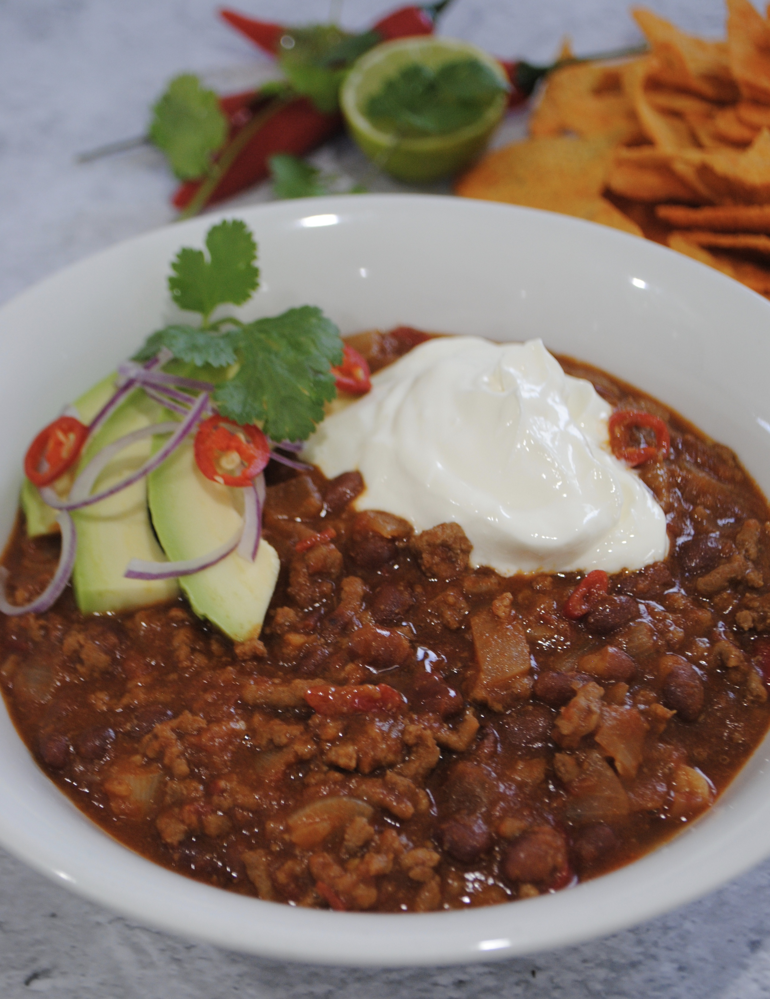 Smokey Chilli Con Carne served in a bowl with sour cream and guacamole