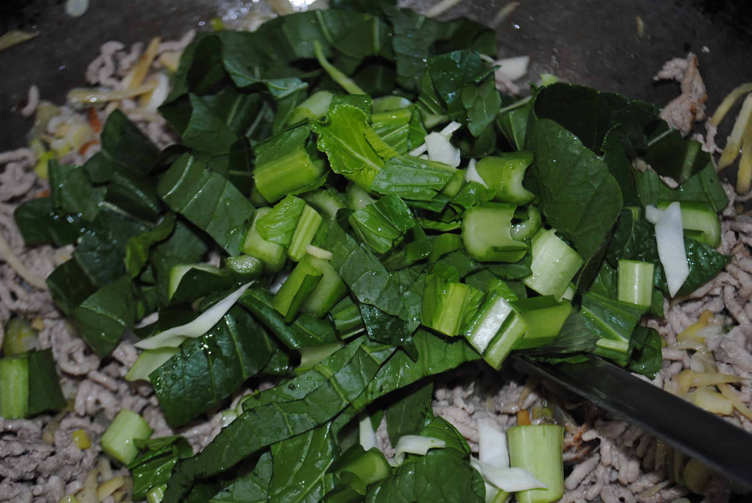 choy sum being added to pork and aromatics in wok for stir fried pork and sesame udon noodles