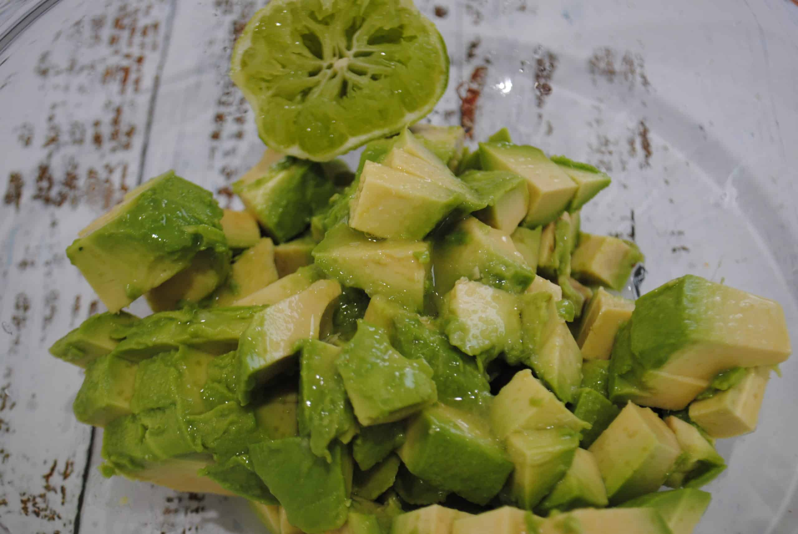 guacamole avocado preparation with cubed avocado and lime juice added with squeezed lime half in bowl