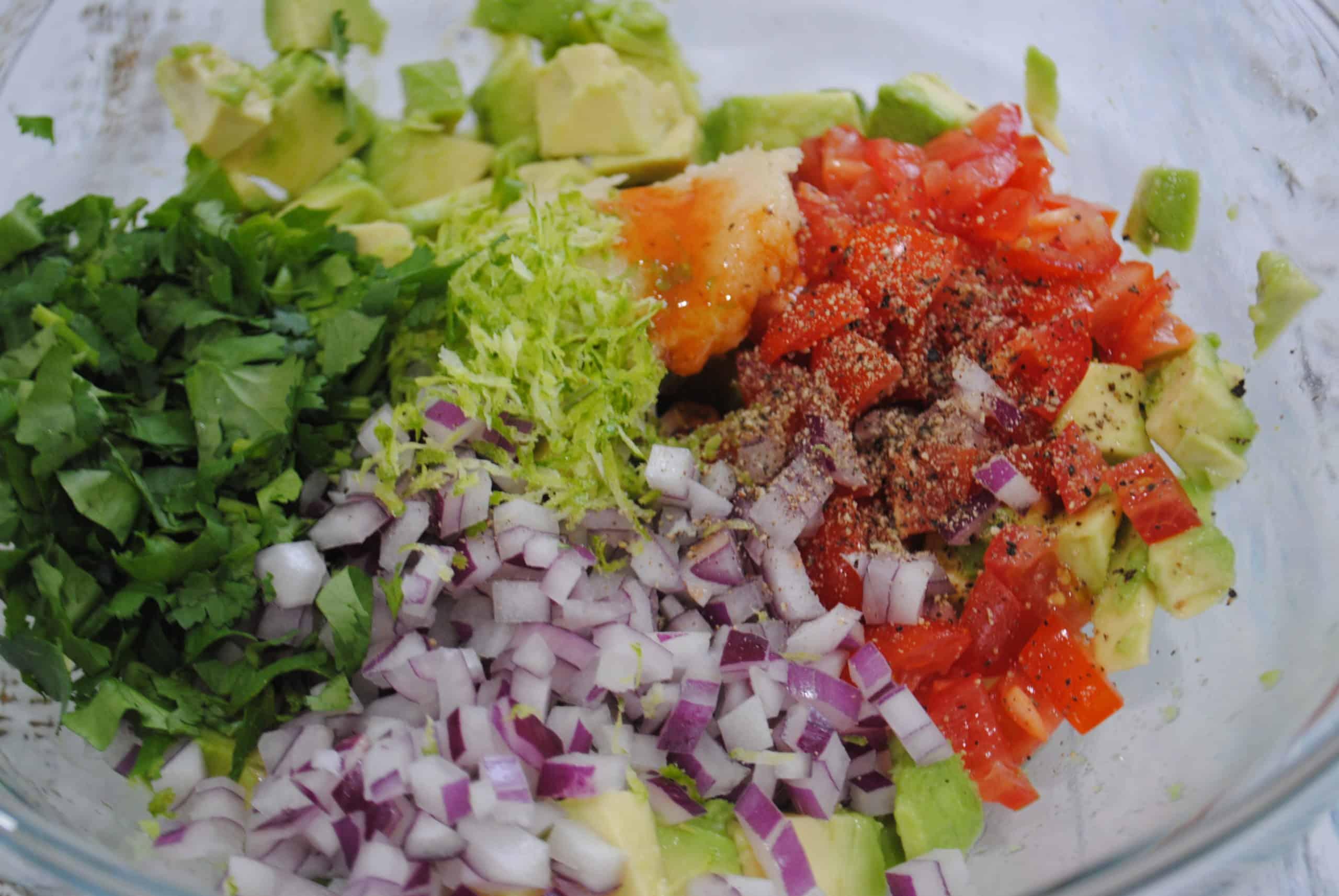 guacamole preparation with onion, tomato, coriander, garlic, lime zest, tabasco added to bowl ready to mix through