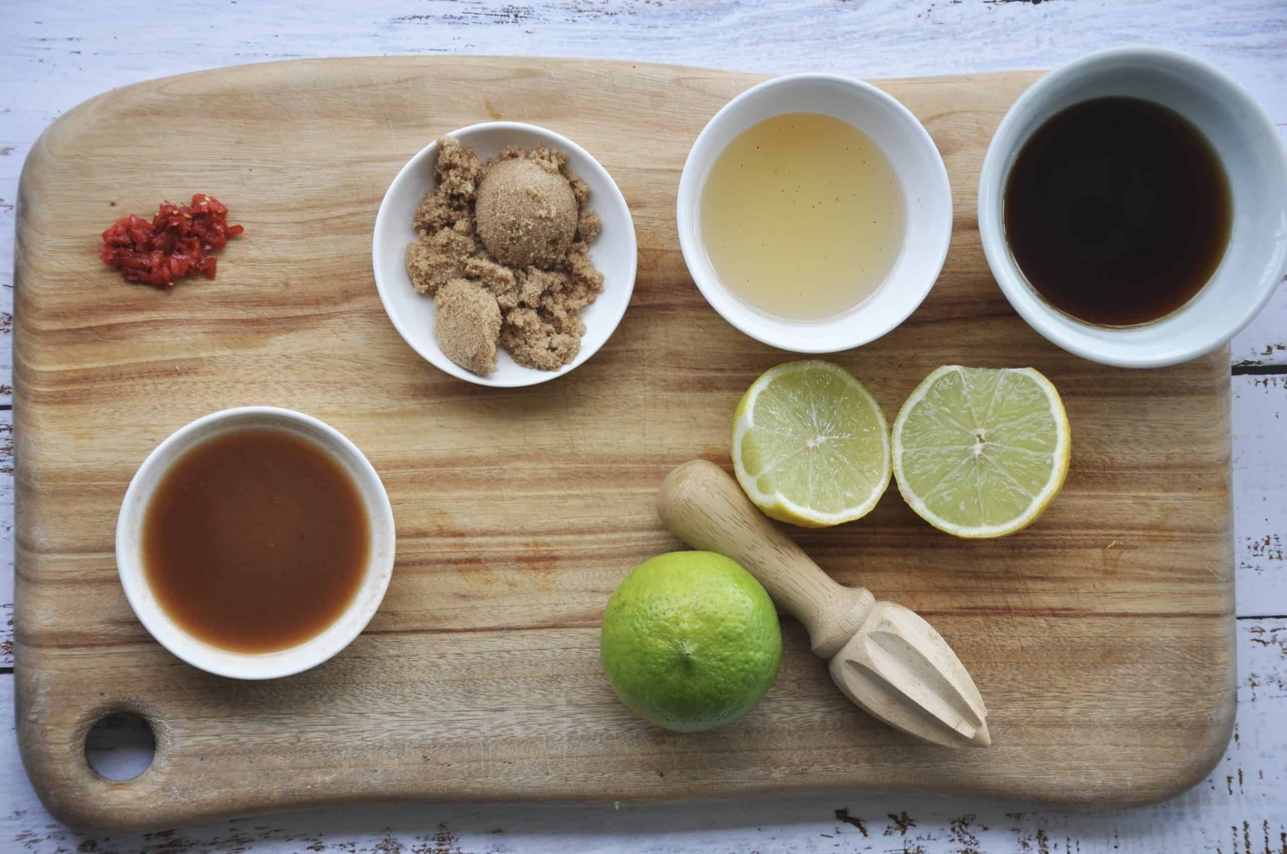 dressing ingredients on a wooden chopping board to make thai chicken larb