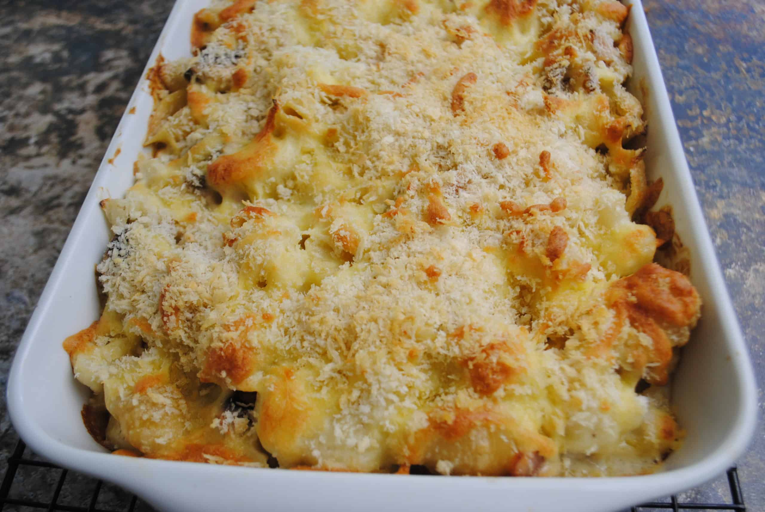 cauliflower pasta bake with bacon and mushrooms cooked in a white rectangular dish ready to serve