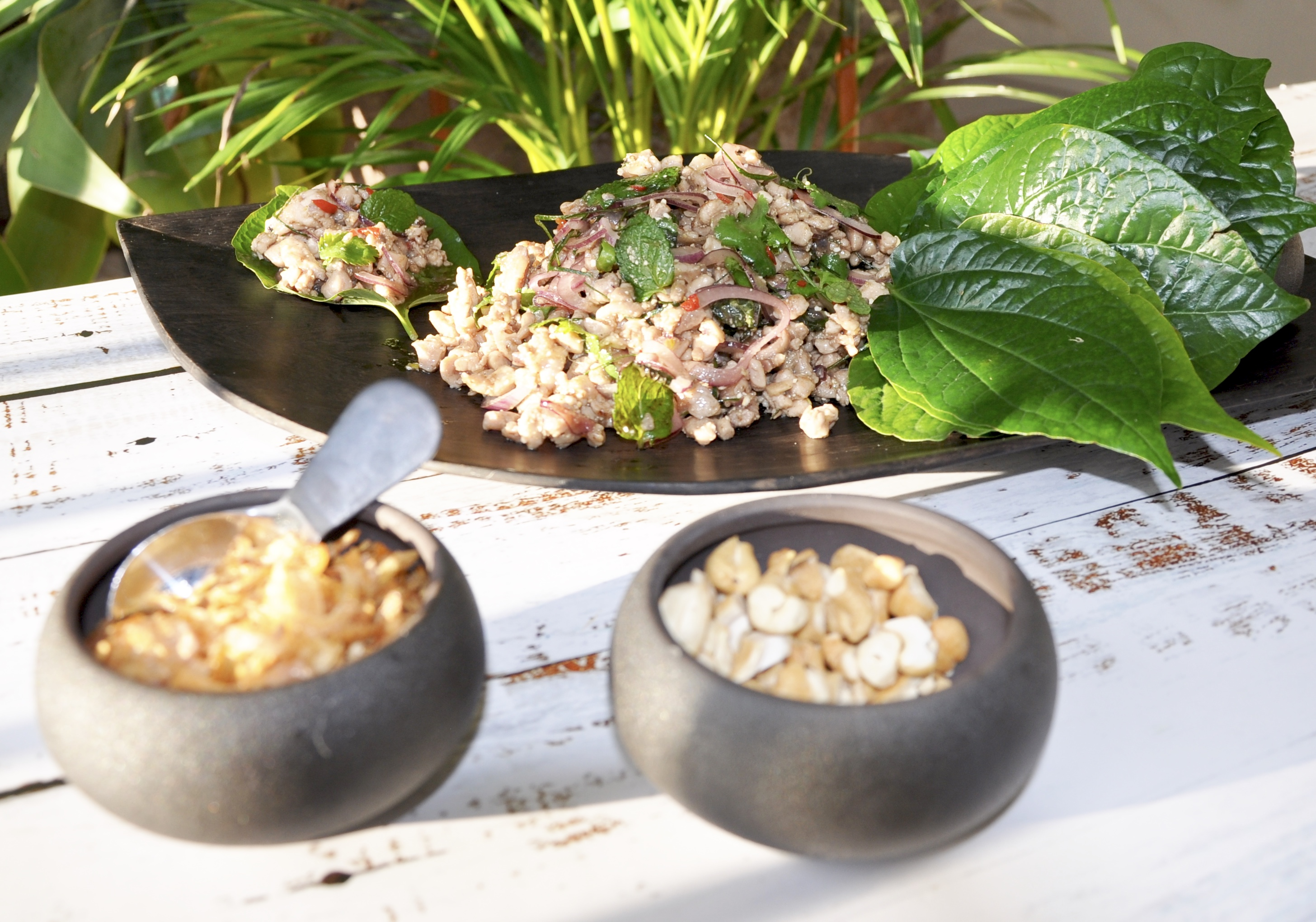 Thai chicken larb salad cooked and served on a somber plate with betel leaves and 2 bowls with fried shallots and cashew nuts