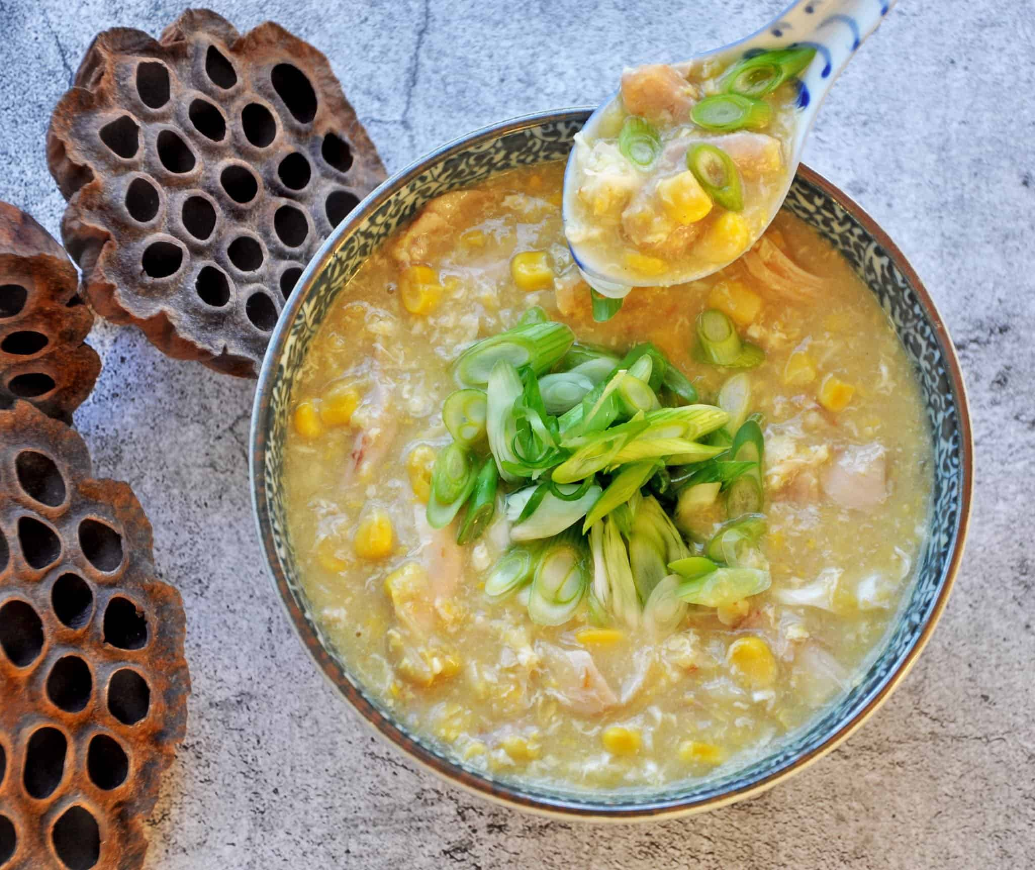 CHICKEN AND SWEET CORN SOUP WITH SHALLOTS SERVED A BLUE BOWL WITH SPOON DIPPING INTO SOUP