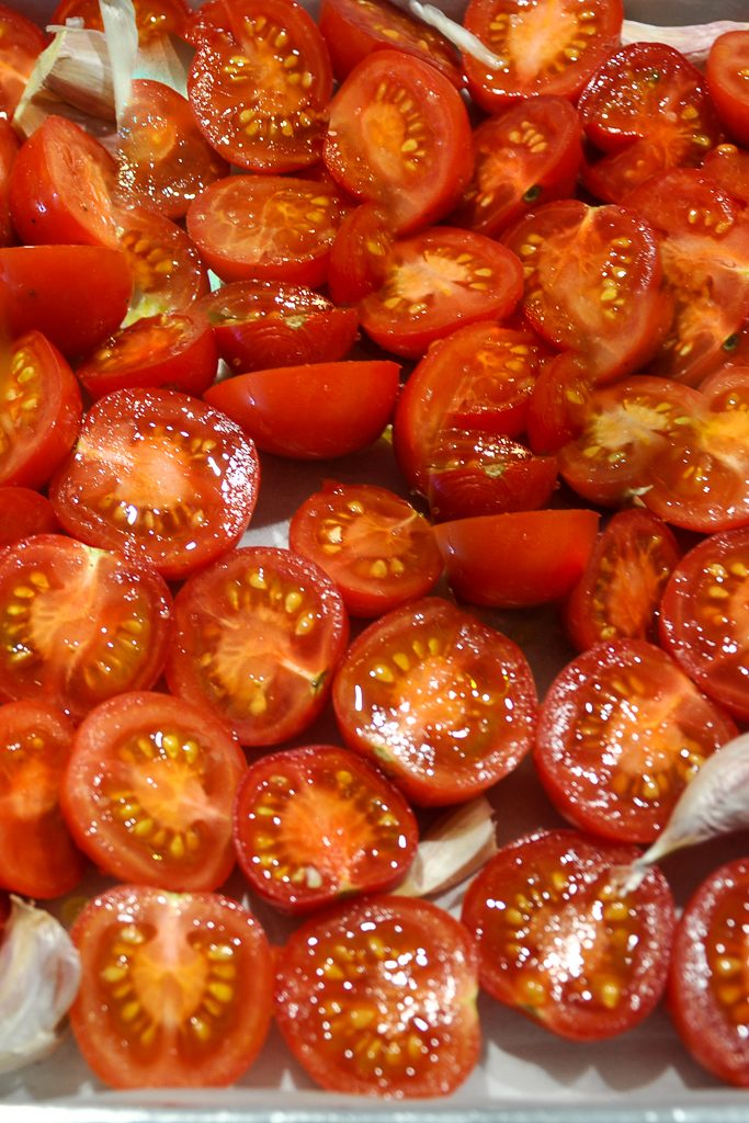 Tomatoes and garlic for roasted tomato and garlic soup on a silver tray ready to bake