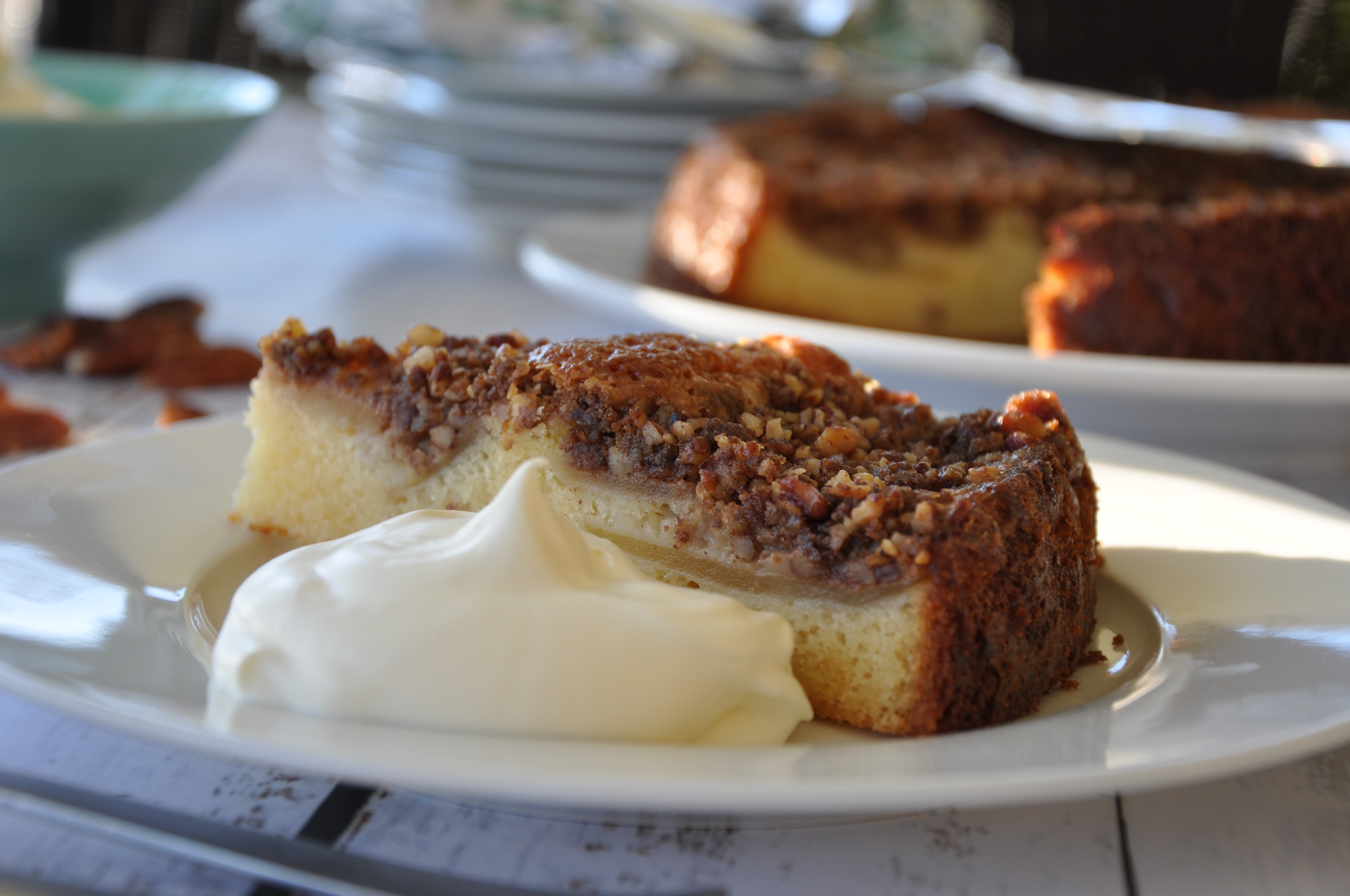 Apple pecan cake slice served on a white plate with whole cake in the background