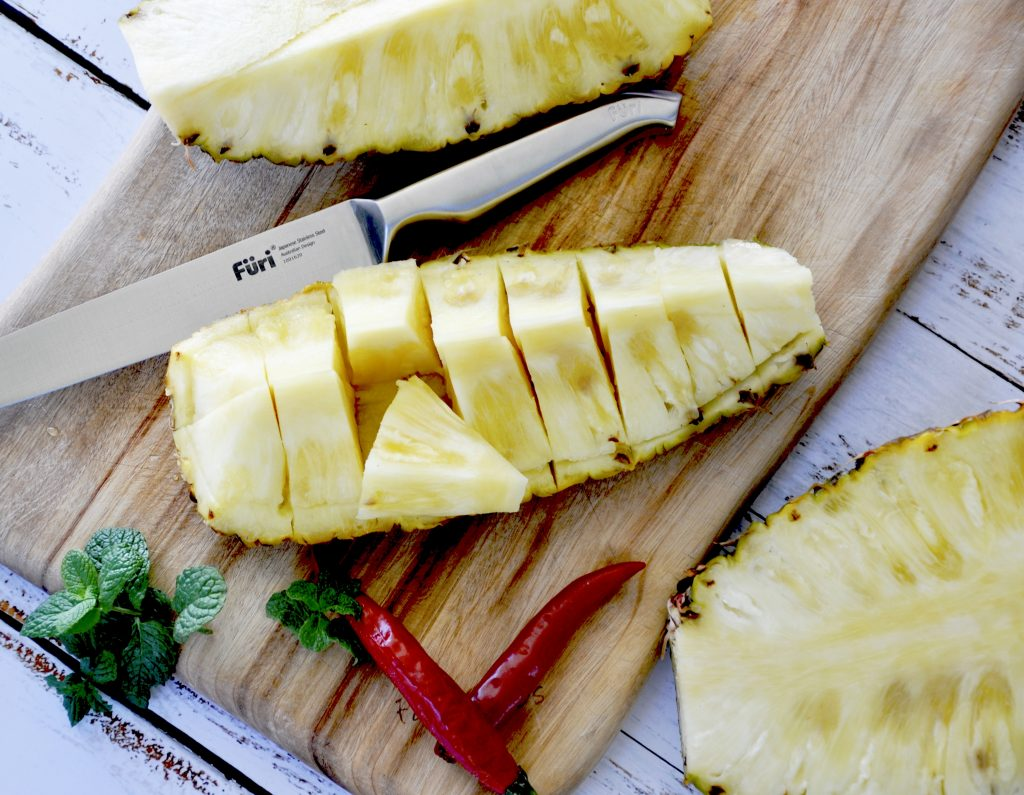 pineapple, mint and chilli sorbet fresh pineapple cut on chopping board with knife, chilli and mint