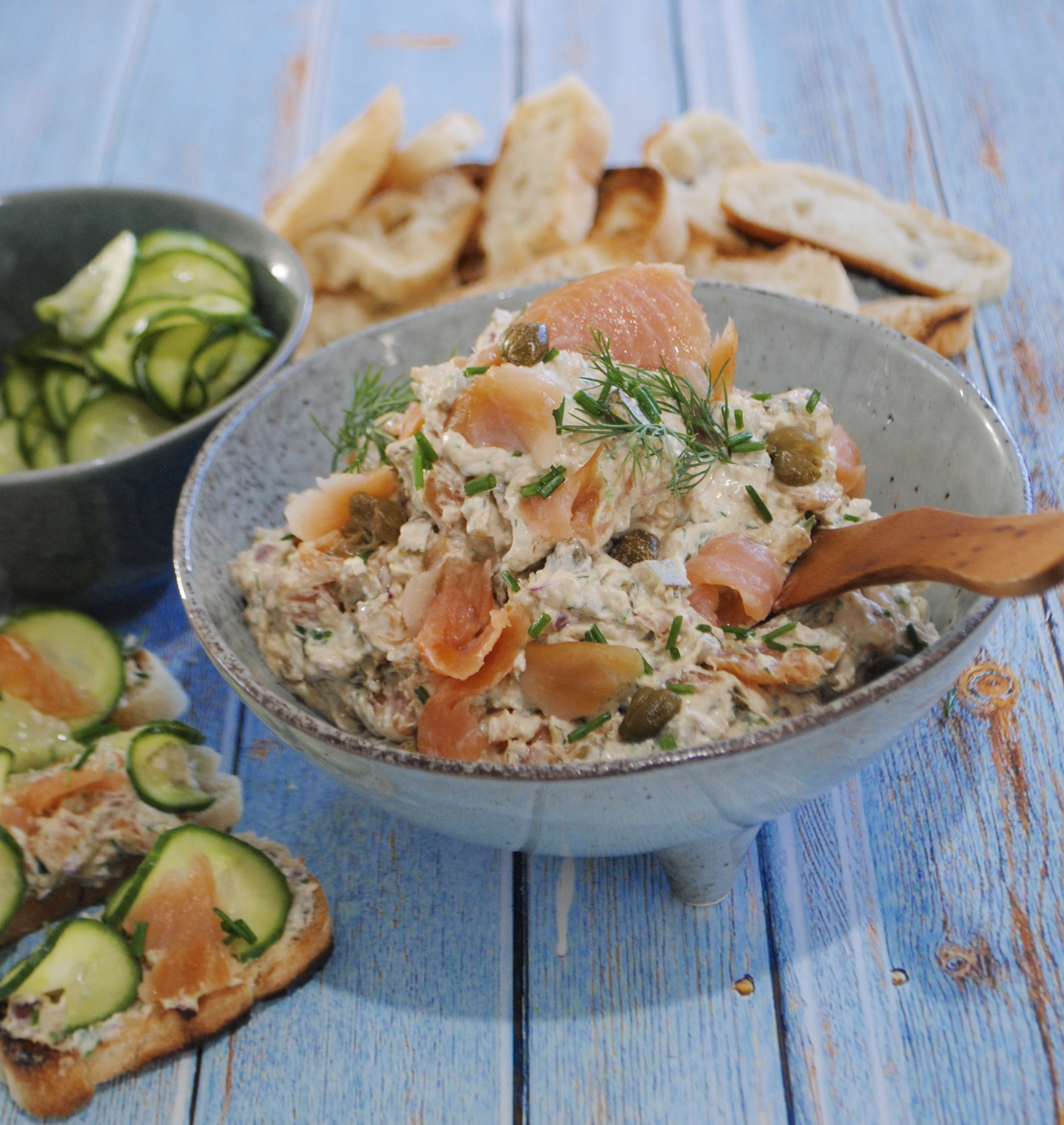 smoked salmon pate with quick pickled cucumbers ready to serve in a bowl with toast in the background and pickled cucumbers