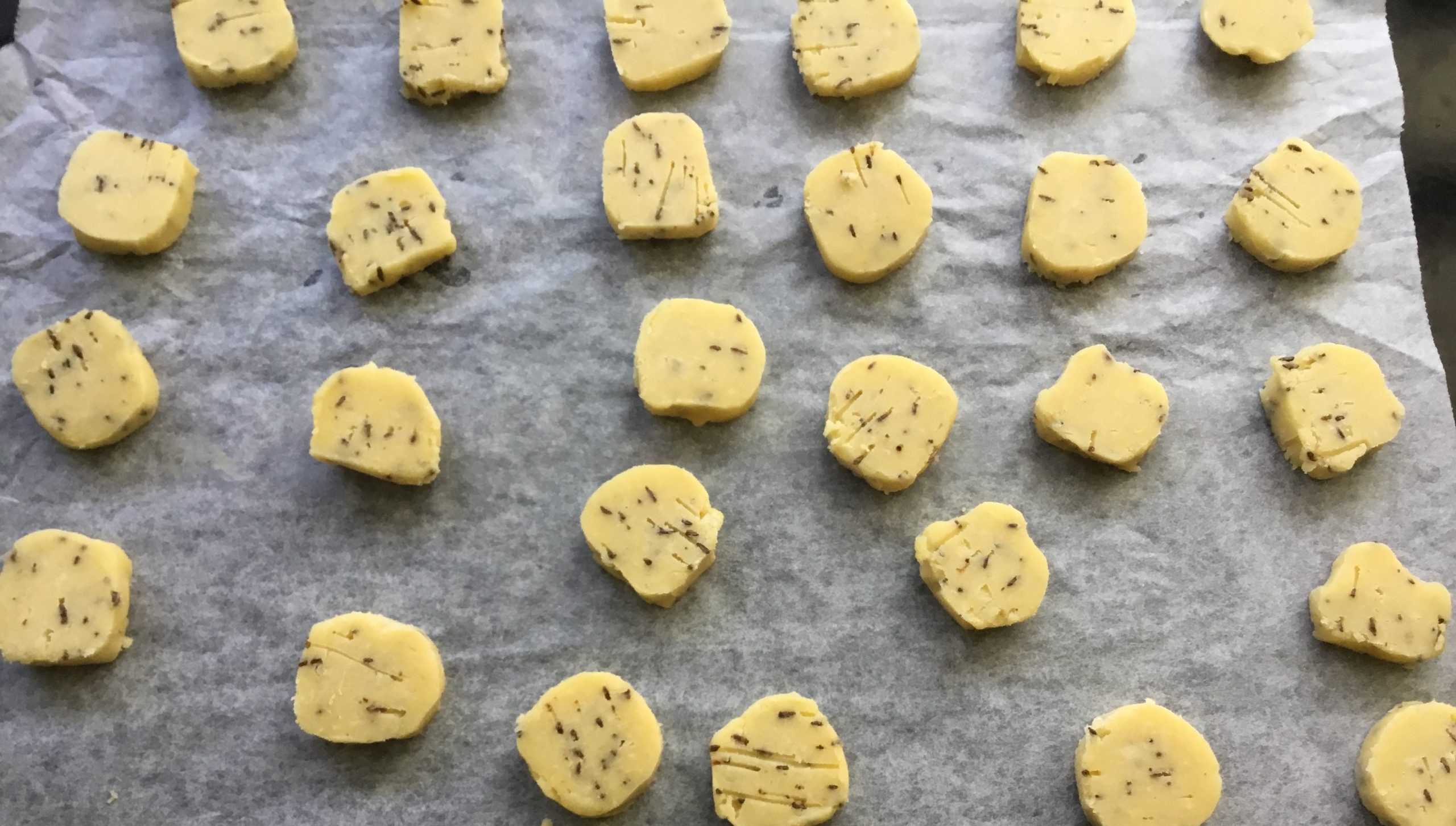 cheese and caraway shortbread biscuits sliced and on baking tray ready to bake