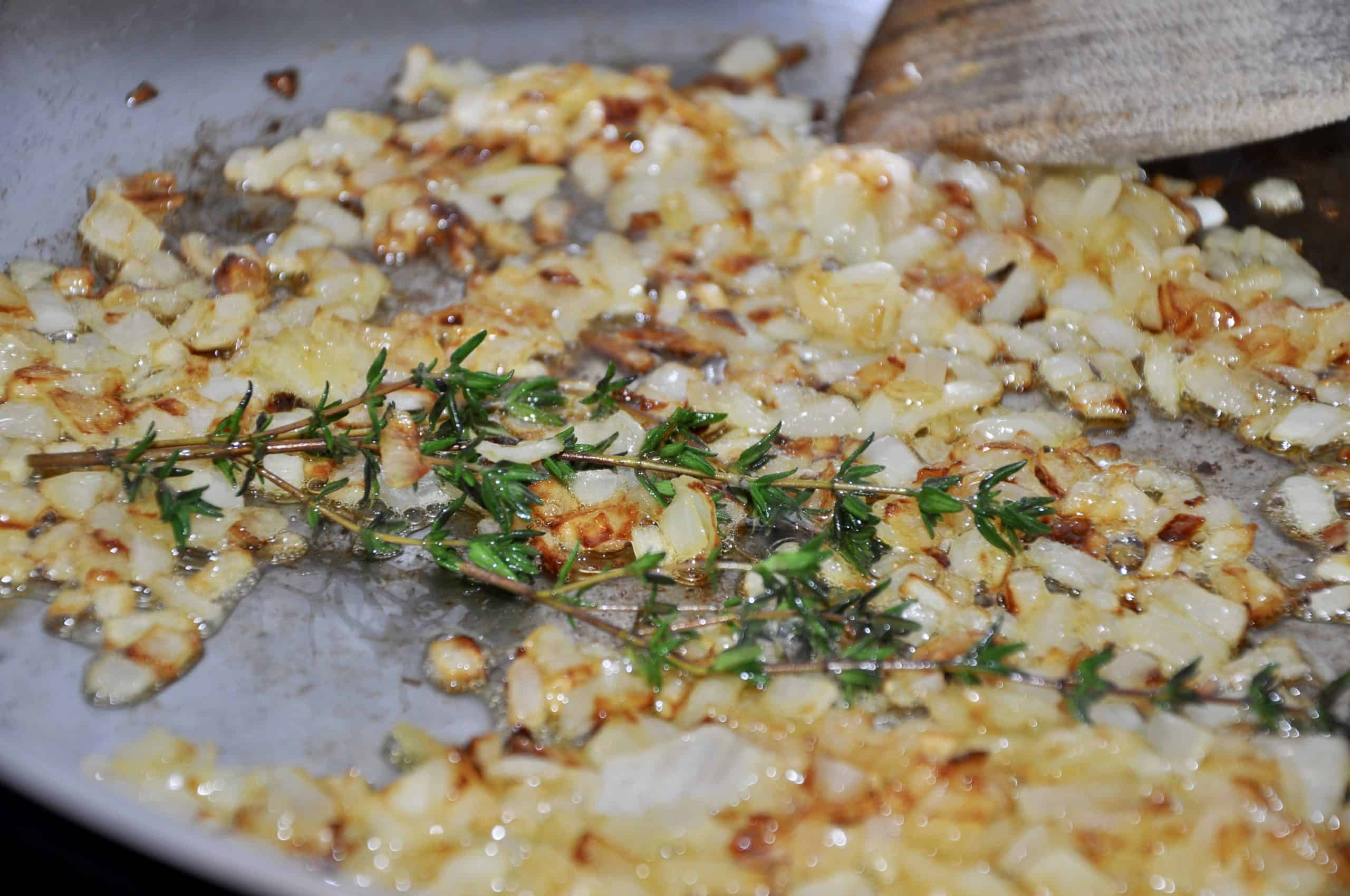 golden onions frying in butter with thyme to make Roasted tomato and garlic soup