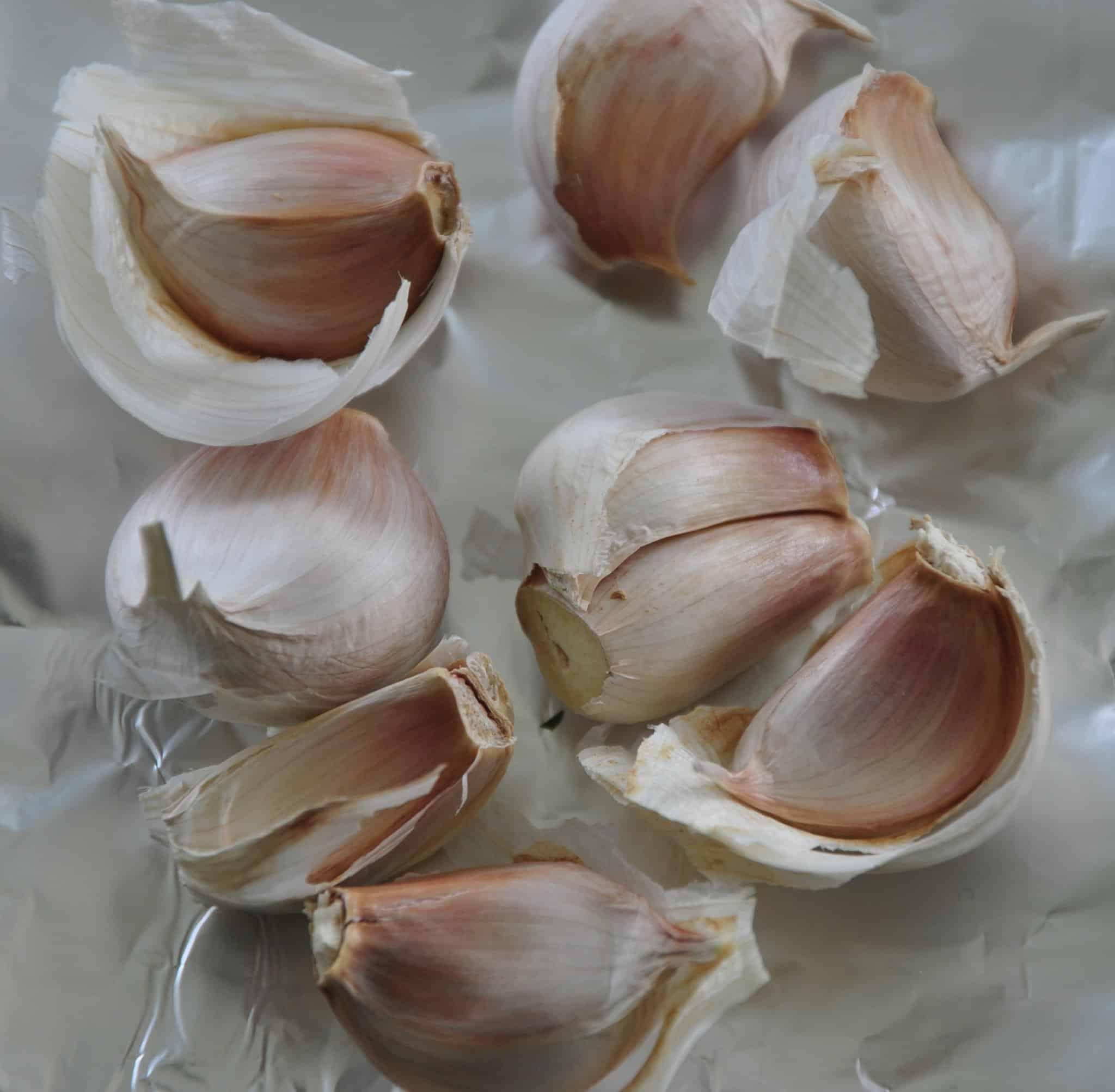 roasted garlic, anchovy and caper dressing fresh garlic on aluminium foil