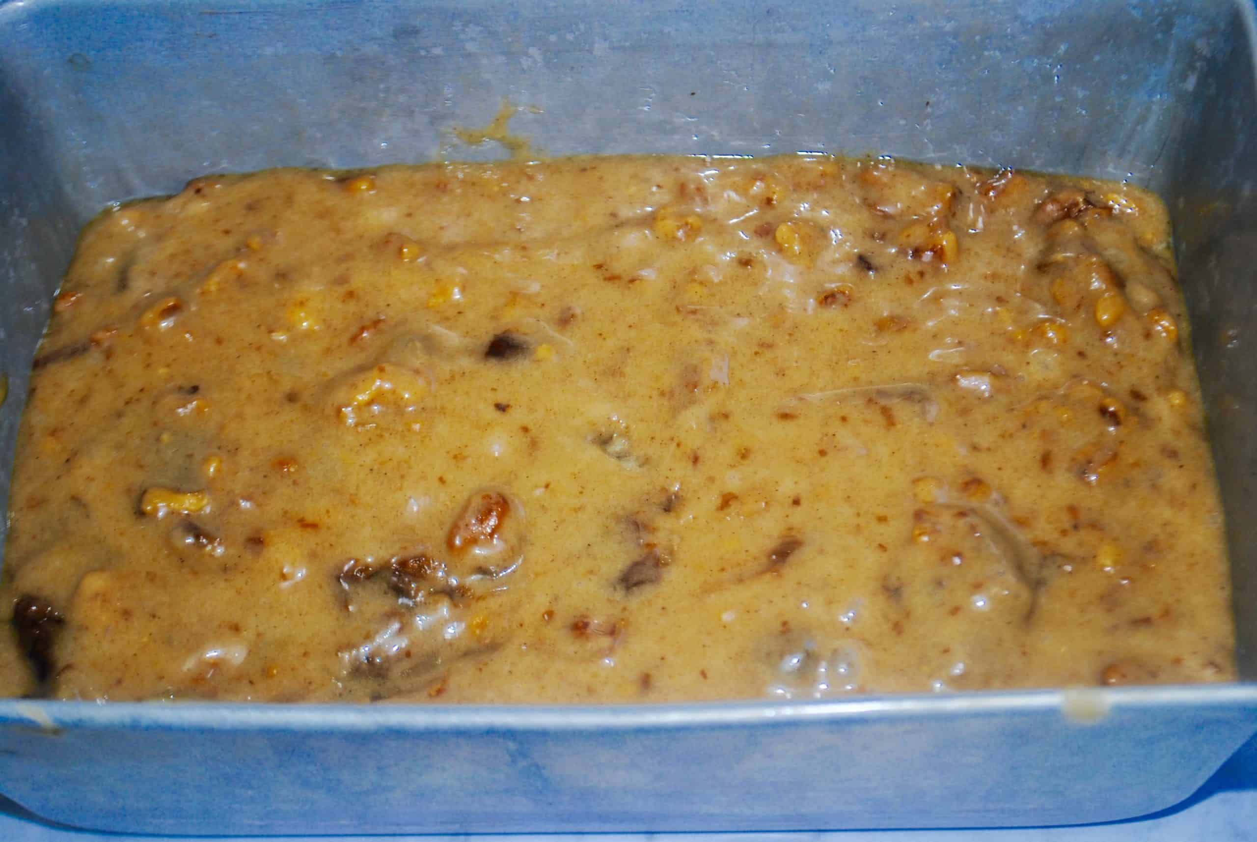 date and walnut cake mixture poured into a silver tin ready to bake