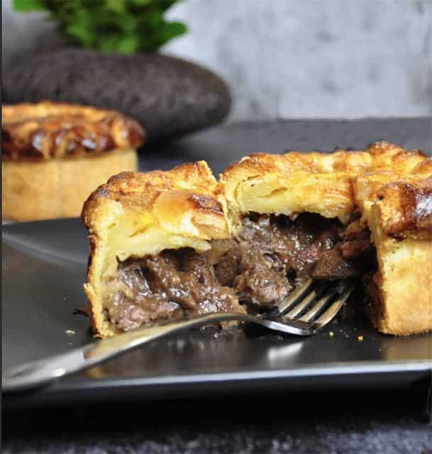 Beef Bourguignon Pie cut open and resting on a dark plate