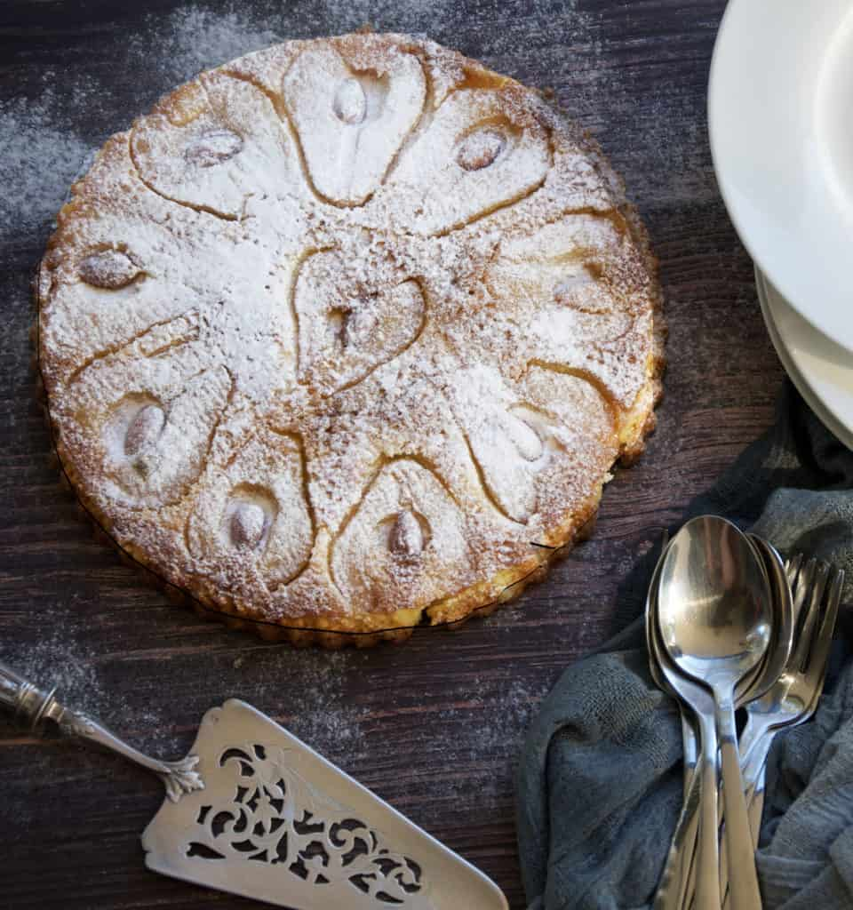 pear and almond crustless tart - gluten free ready to serve on a wooden board with cutlery