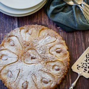 pear and almond crustless tart served on a wooden board with white plates and a serving knife
