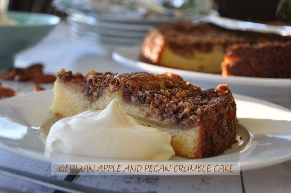 German apple and pecan crumble cake on a white plate with a dollop of cream