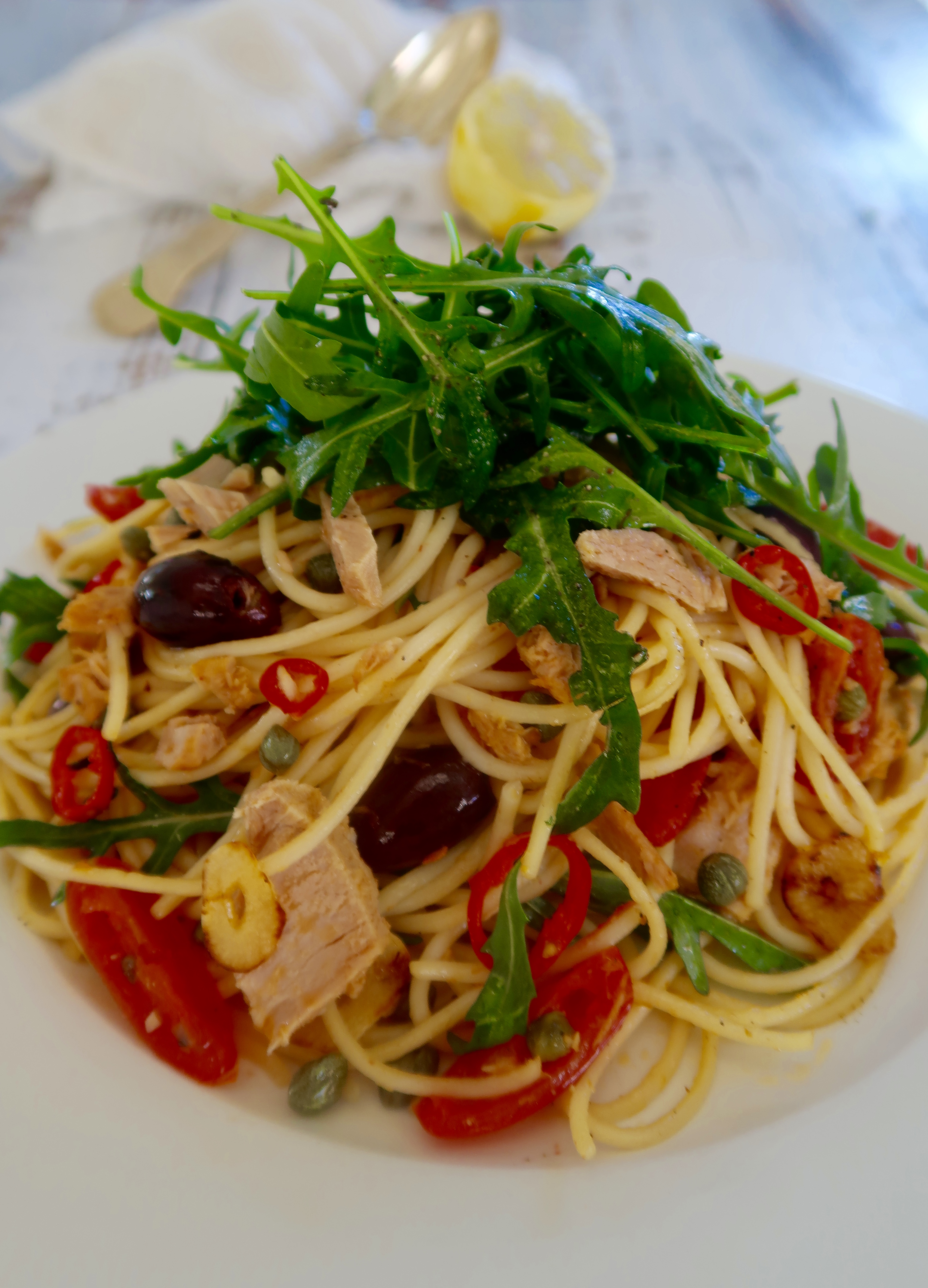 easy quick tuna pasta served on a white plate with fresh rocket on top of pasta and cut lemon in the background