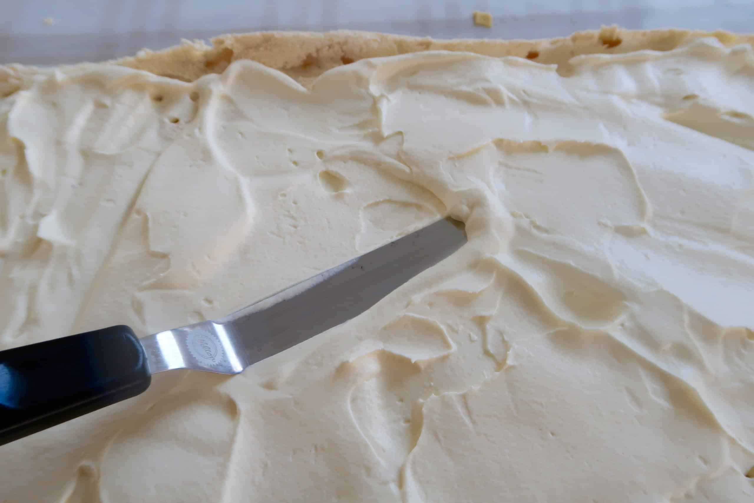 easy strawberry pavlova spreading whipped cream with a metal spatula