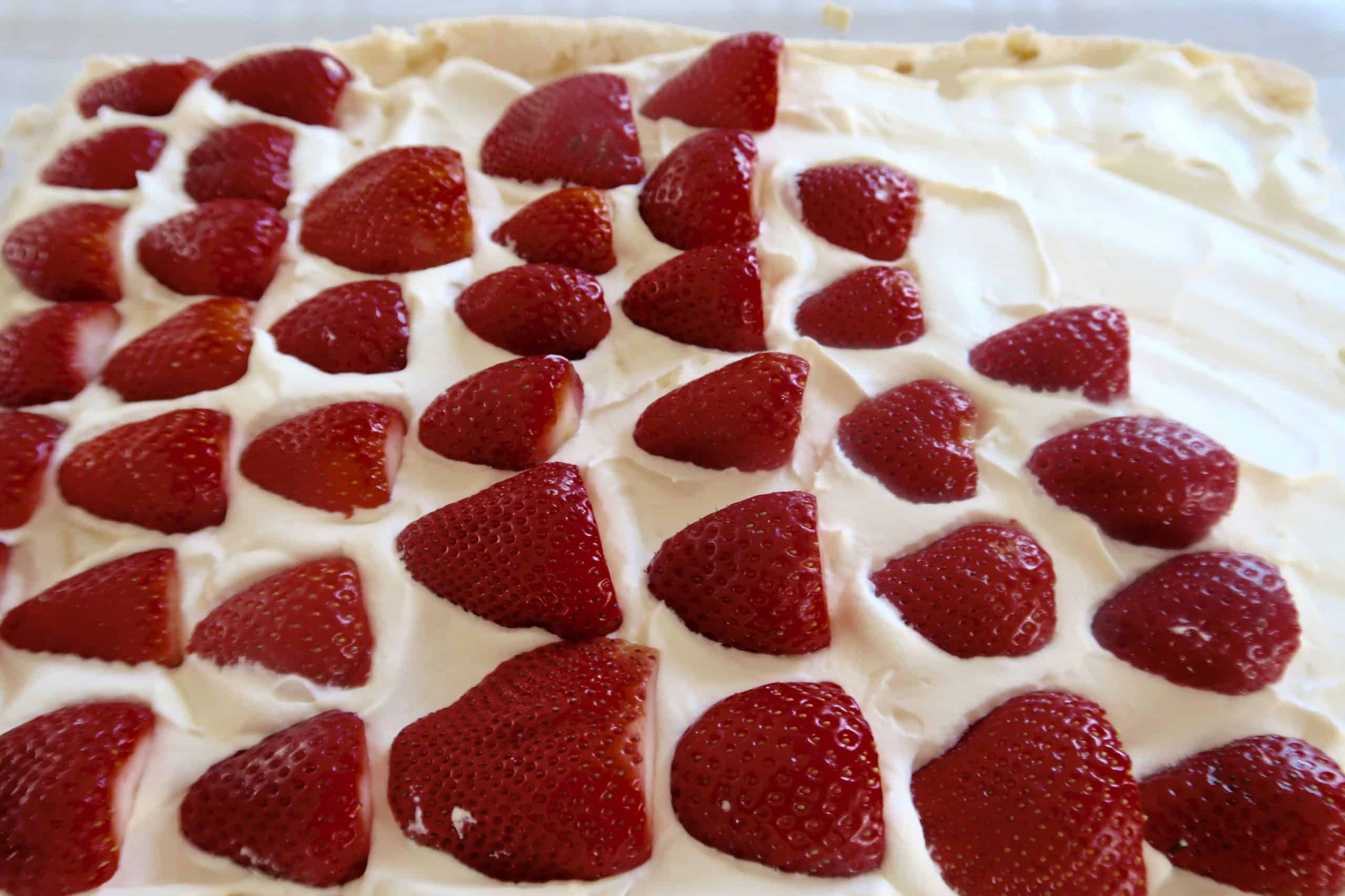 easy strawberry pavlova placing halved strawberries on top of cream