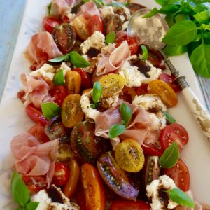 tomato, burrata, basil and prosciutto salad ready to serve with a spoon and basil to the side