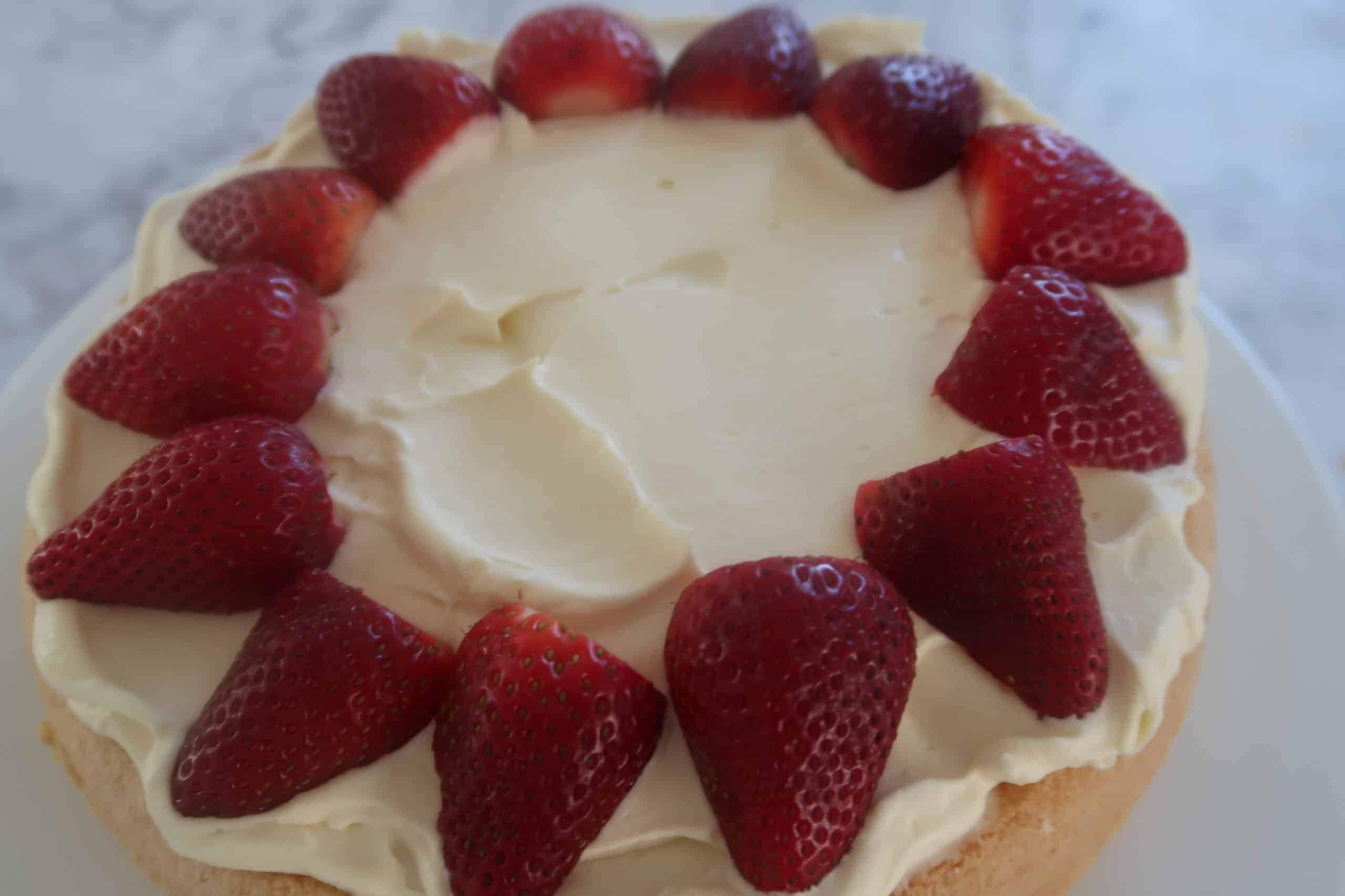 strawberry sponge cake spread with cream and strawberries starting to be placed onto cream