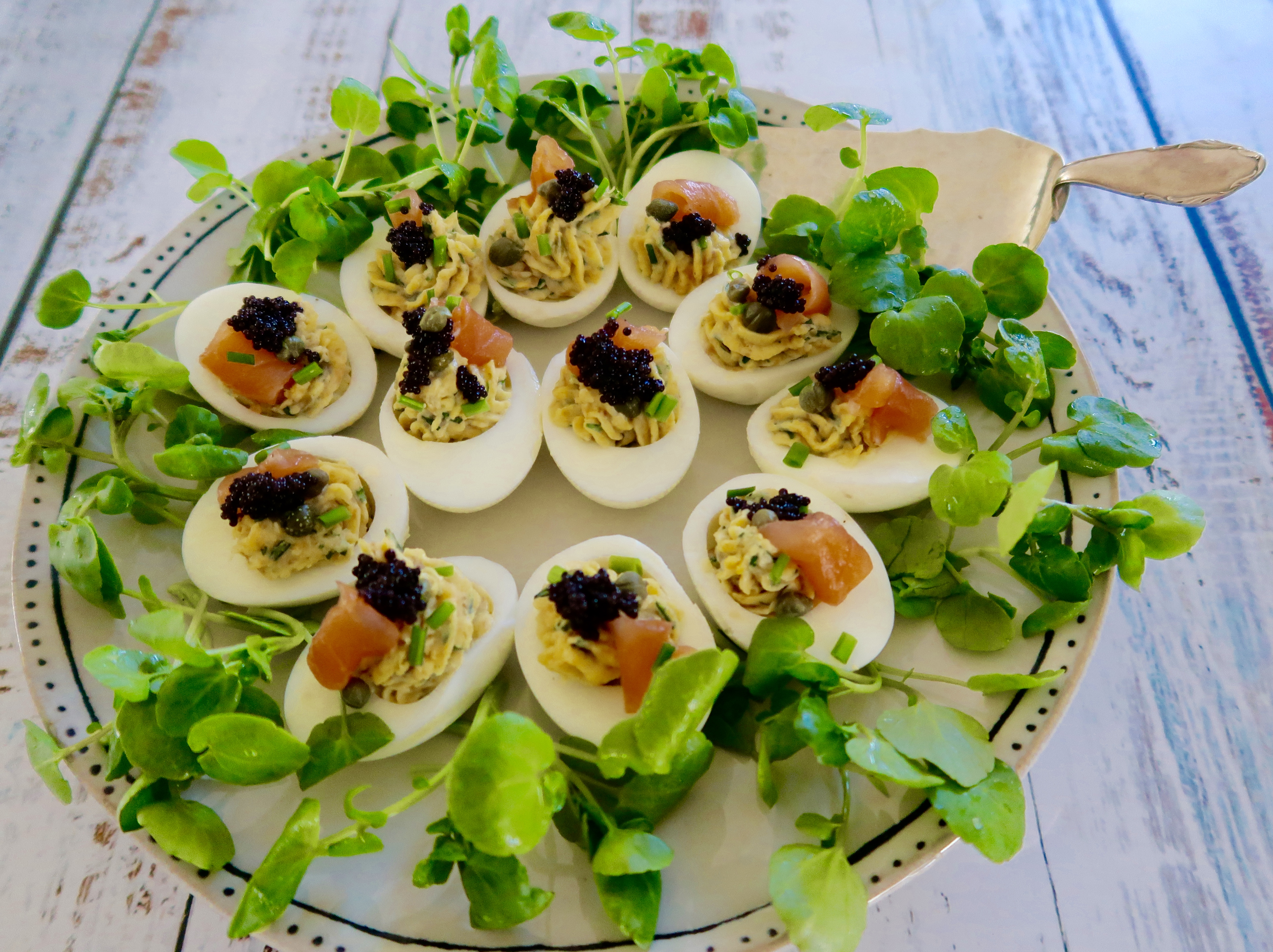 devilled eggs with smoked salmon served on a white plate with black dots on the border and watercress garnish