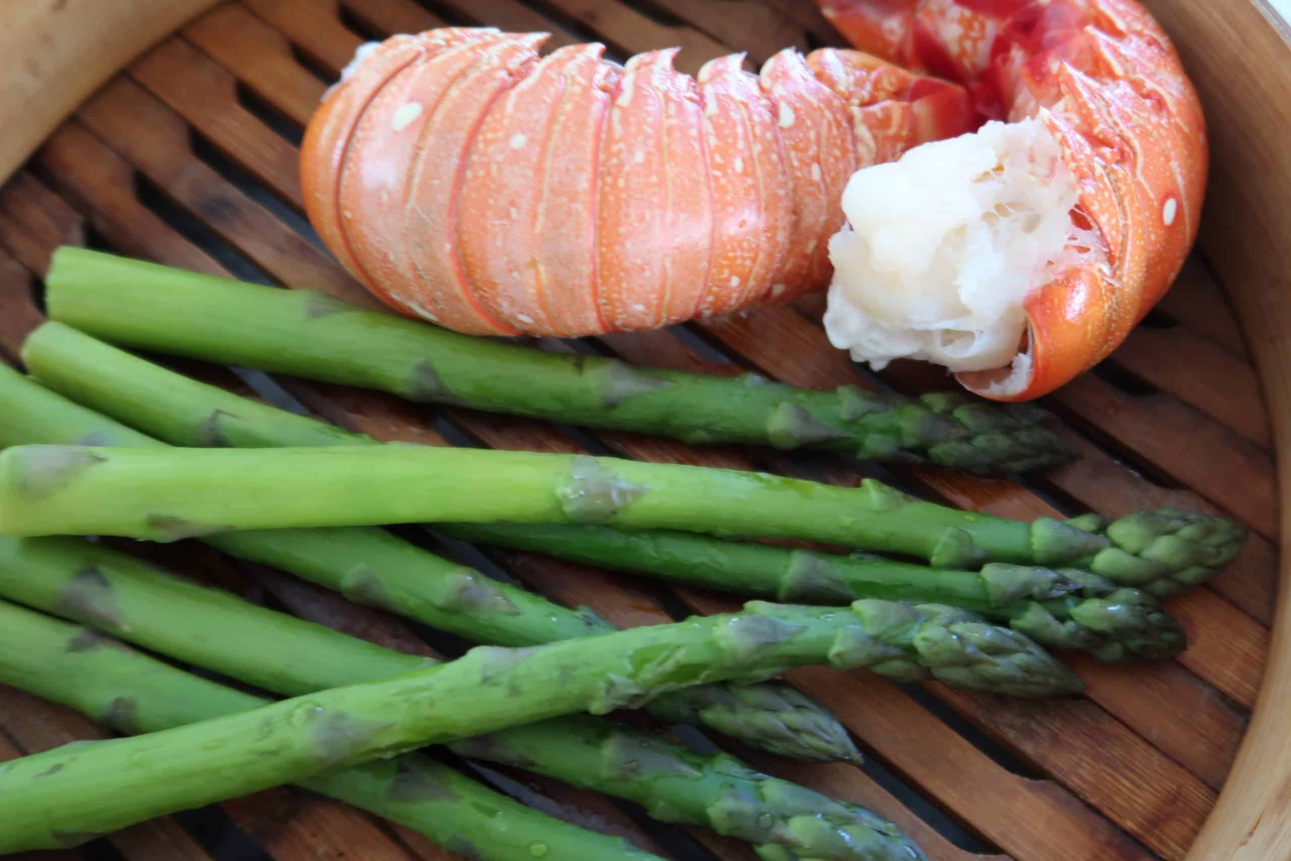 thai mango and lobster salad showing two lobster tails and asparagus spears in a bamboo steamer