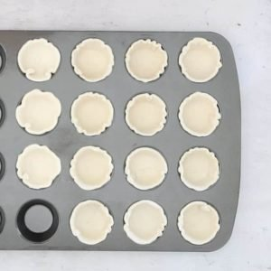 pastry lining a mini muffin tin to make Easy Cheese Puff Tarts
