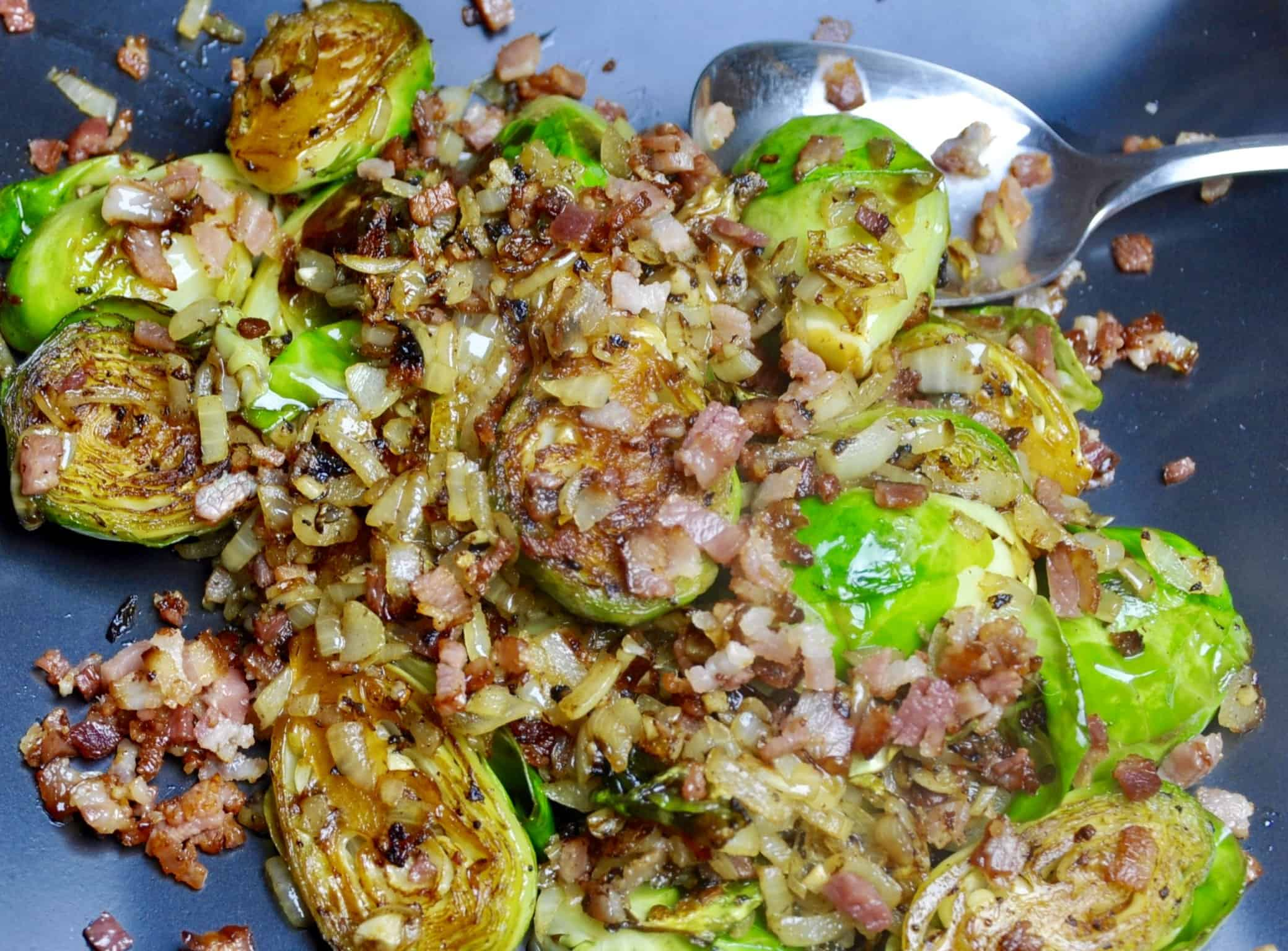 brussel sprouts sauteer with bacon, onion and garlic cooked in a frypan with a silver spoon in the pan
