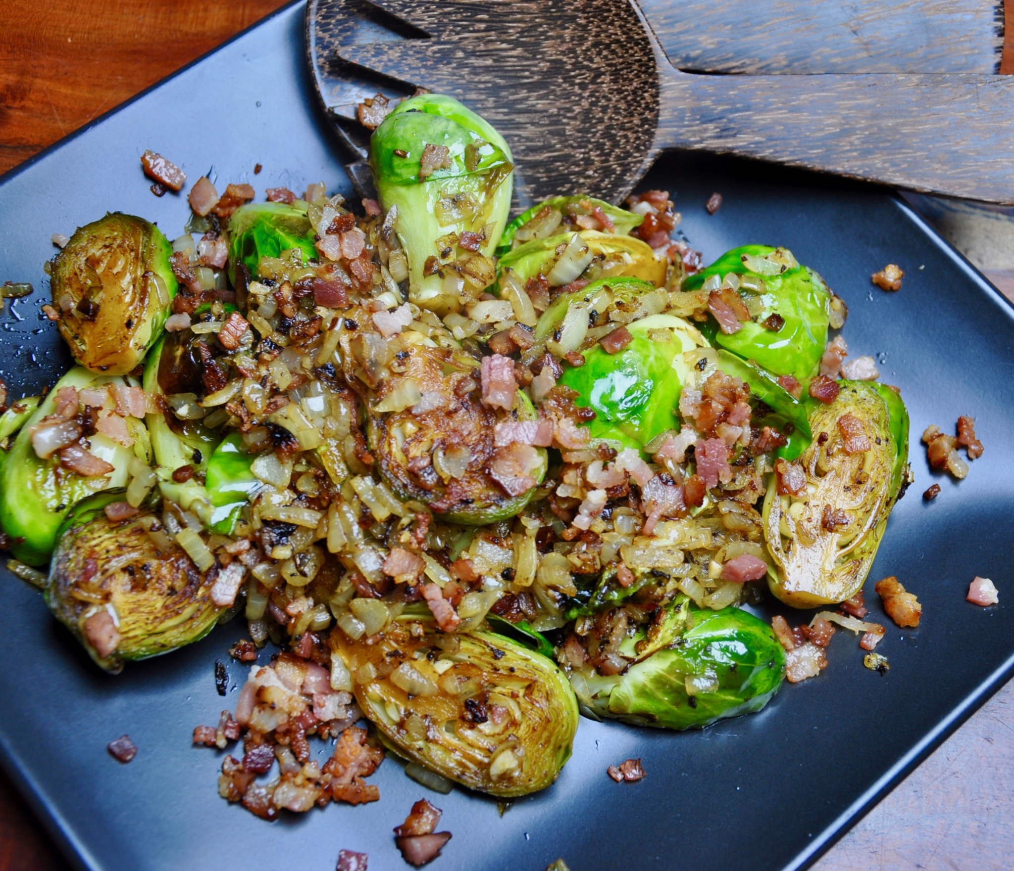 brussel sprouts sauteed with bacon, onion and garlic served on a dark b;i.e. plate with timber fork and spoon servers