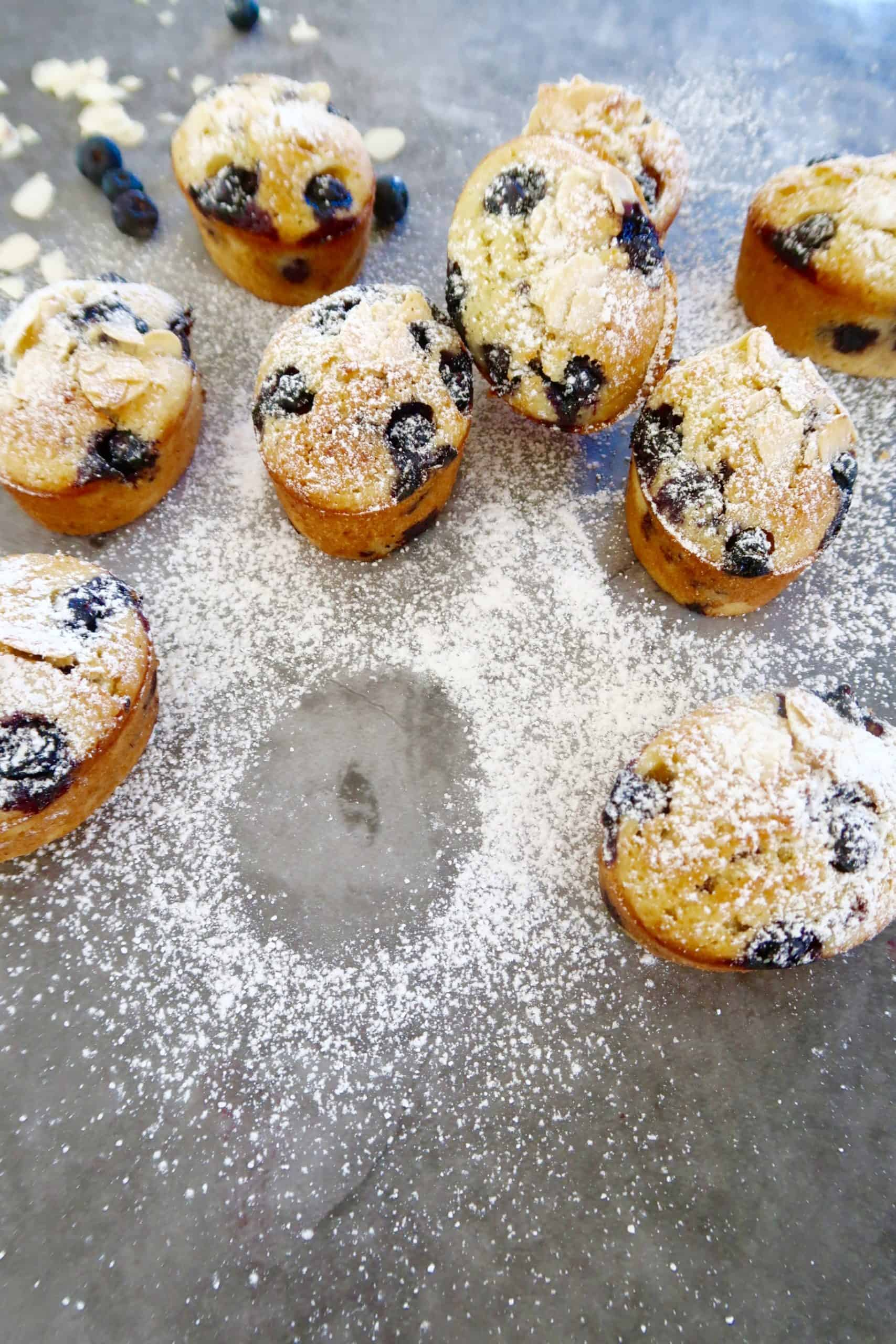blueberry friands with orange zest baked on a bench with sifted icing sugar