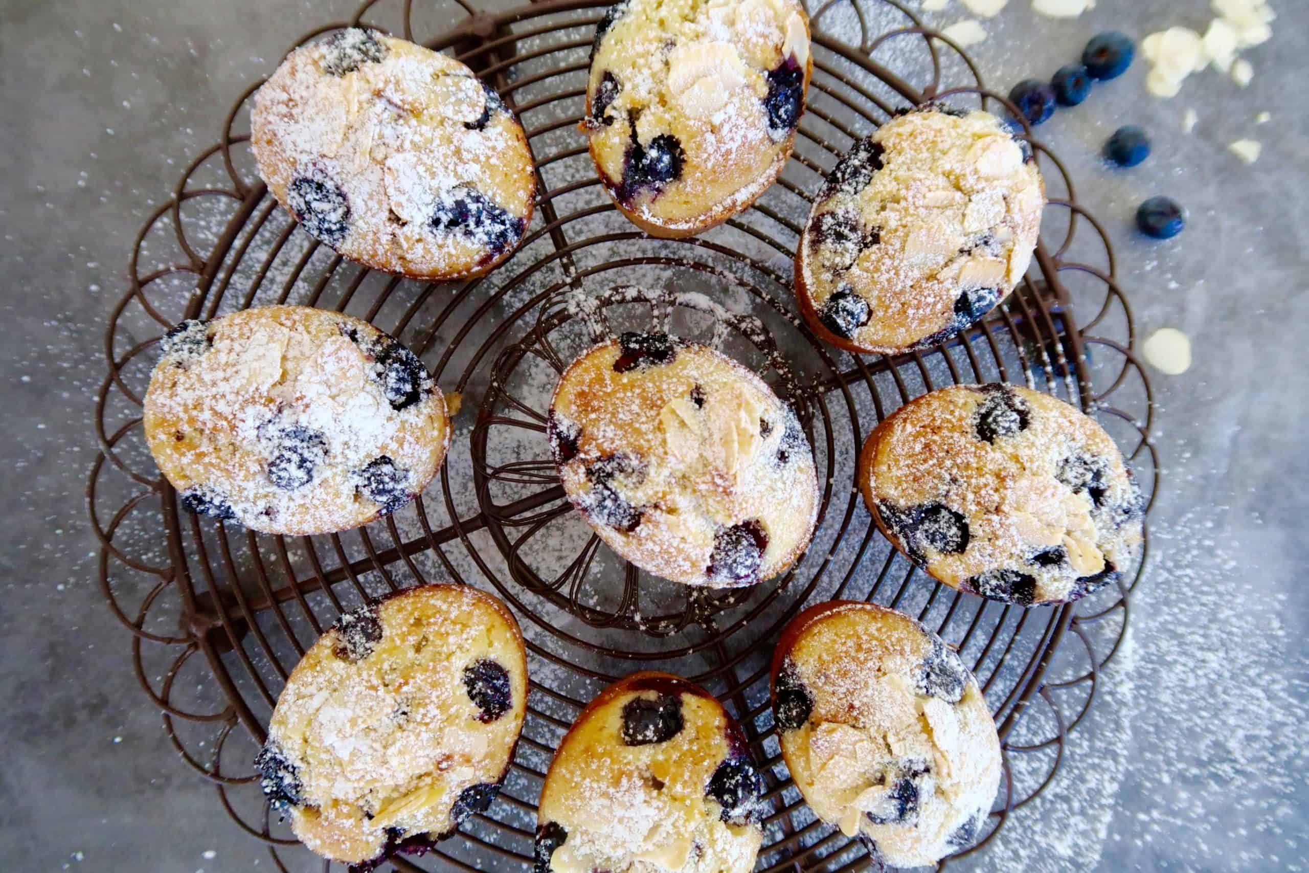 blueberry friands with orange zest baked and dusted with icing sugar on a brown round wire rack