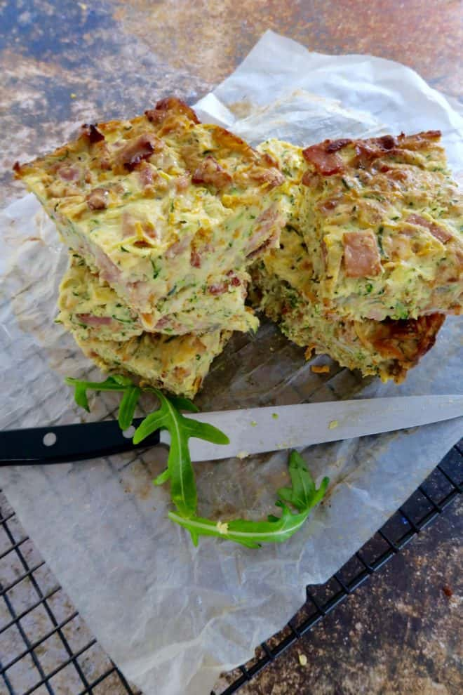 zucchini and bacon slice cooked and cut into squares with a knife sitting on baking paper on a wire cake rack