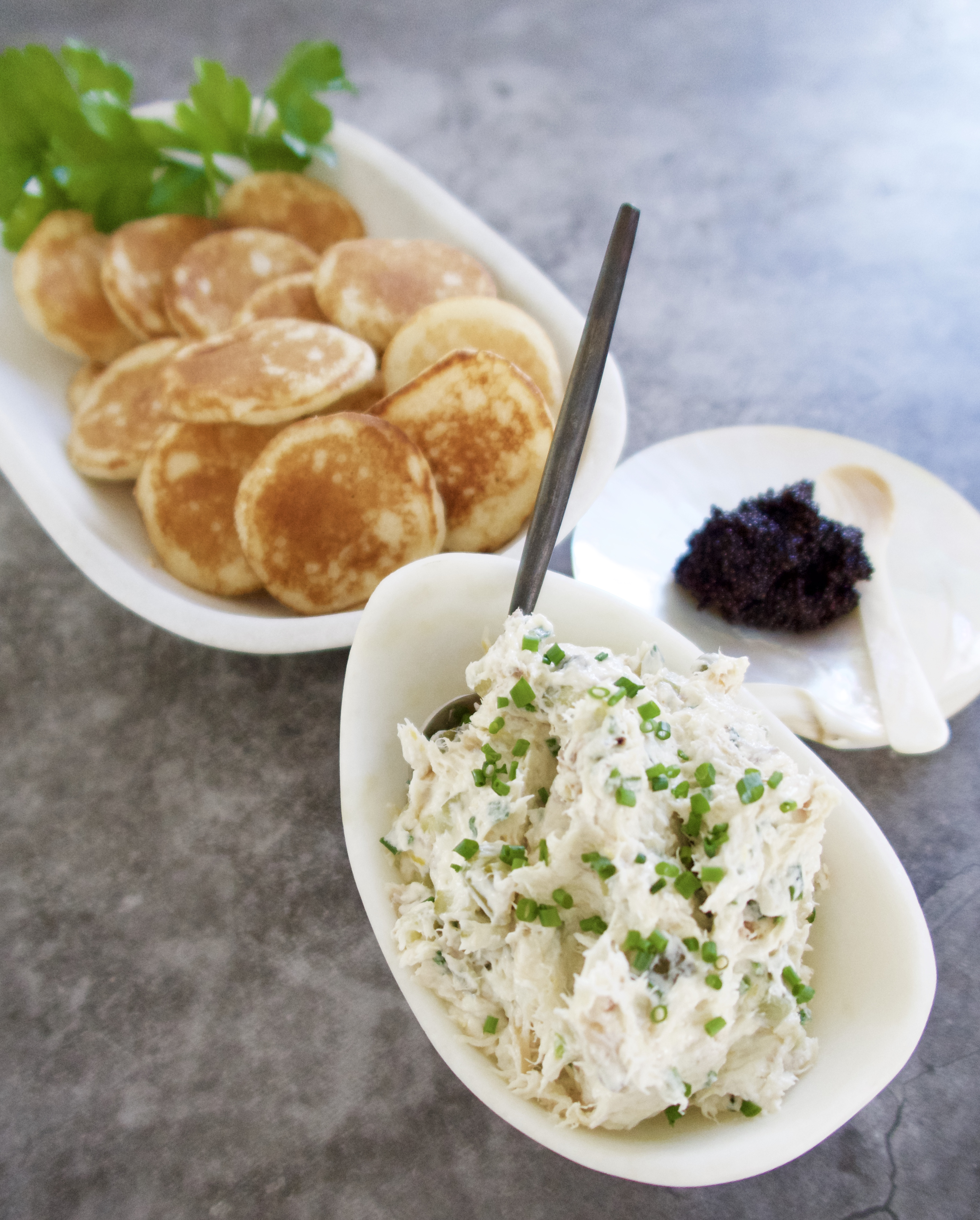 smoked mackerel pate served in an oval marble bowl with a bowl of blinis and a shell with caviar with a shell spoon on a grey background