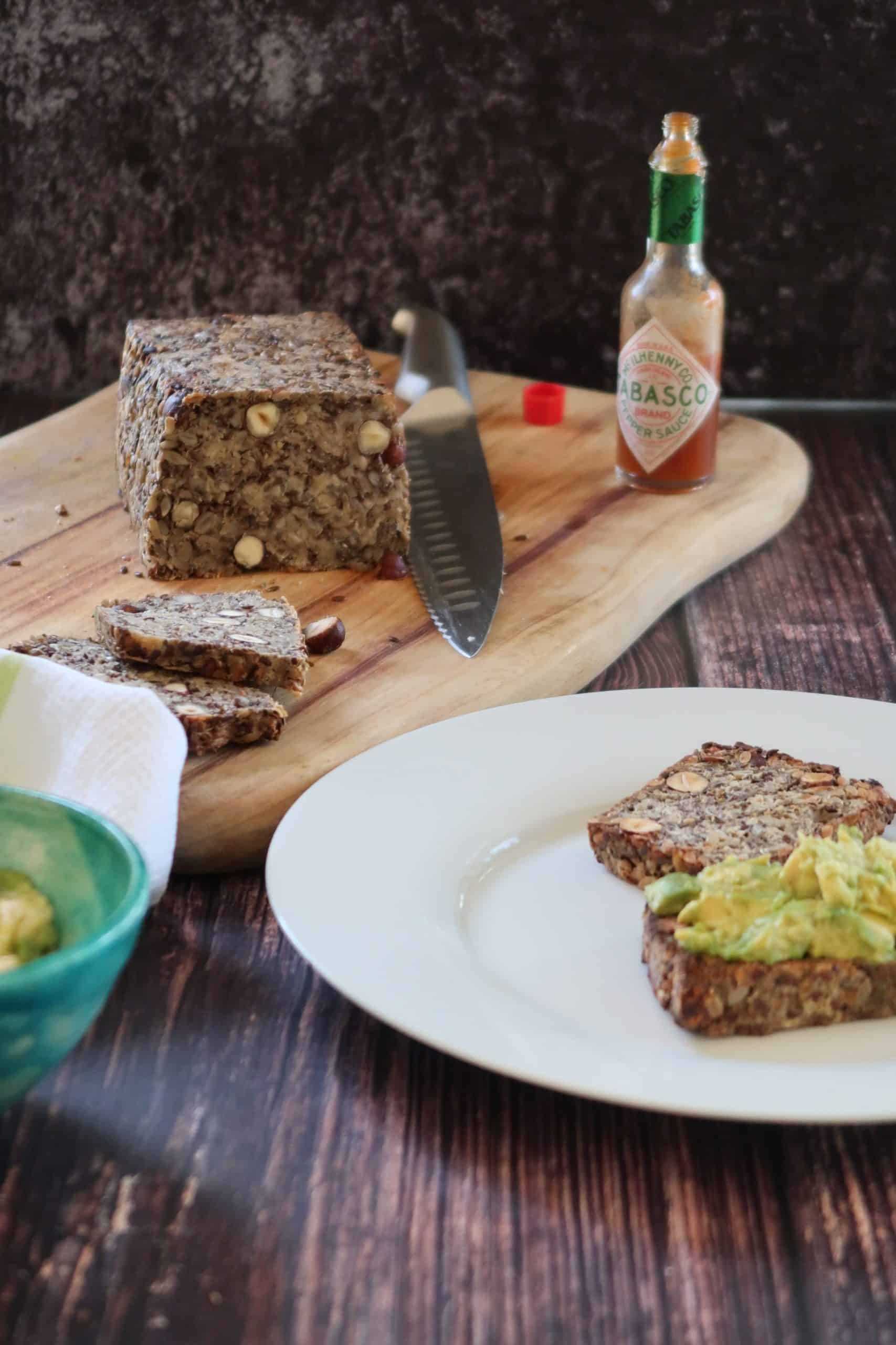 Easy Healthy Grain and Seed Bread - GF V on a timber chopping board with toast on a side plate