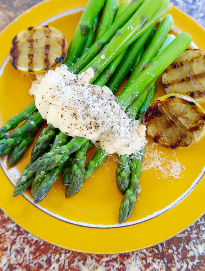 asparagus with parmesan cream served on an orange plate with grilled lime cheeks