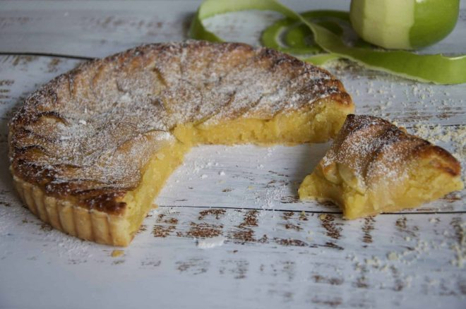 Apple frangipane tart cut with a slice with a bite taken out of it with Apple peel in the background