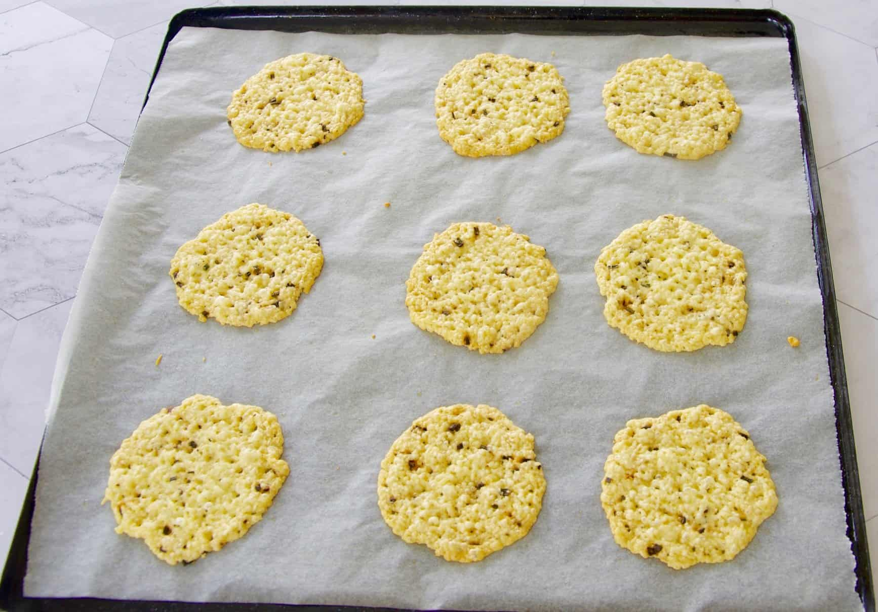 parmesan crisps baked on a tray with baking paper fresh out of the oven